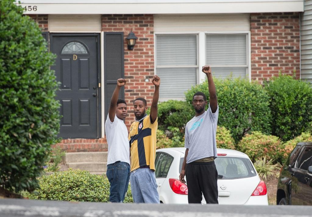 Three youths raise their fists near the site where Keith Lamont Scott was shot by police after a press conference in Charlotte, North Carolina, on September 21, 2016 (AFP Photo/Nicholas Kamm)