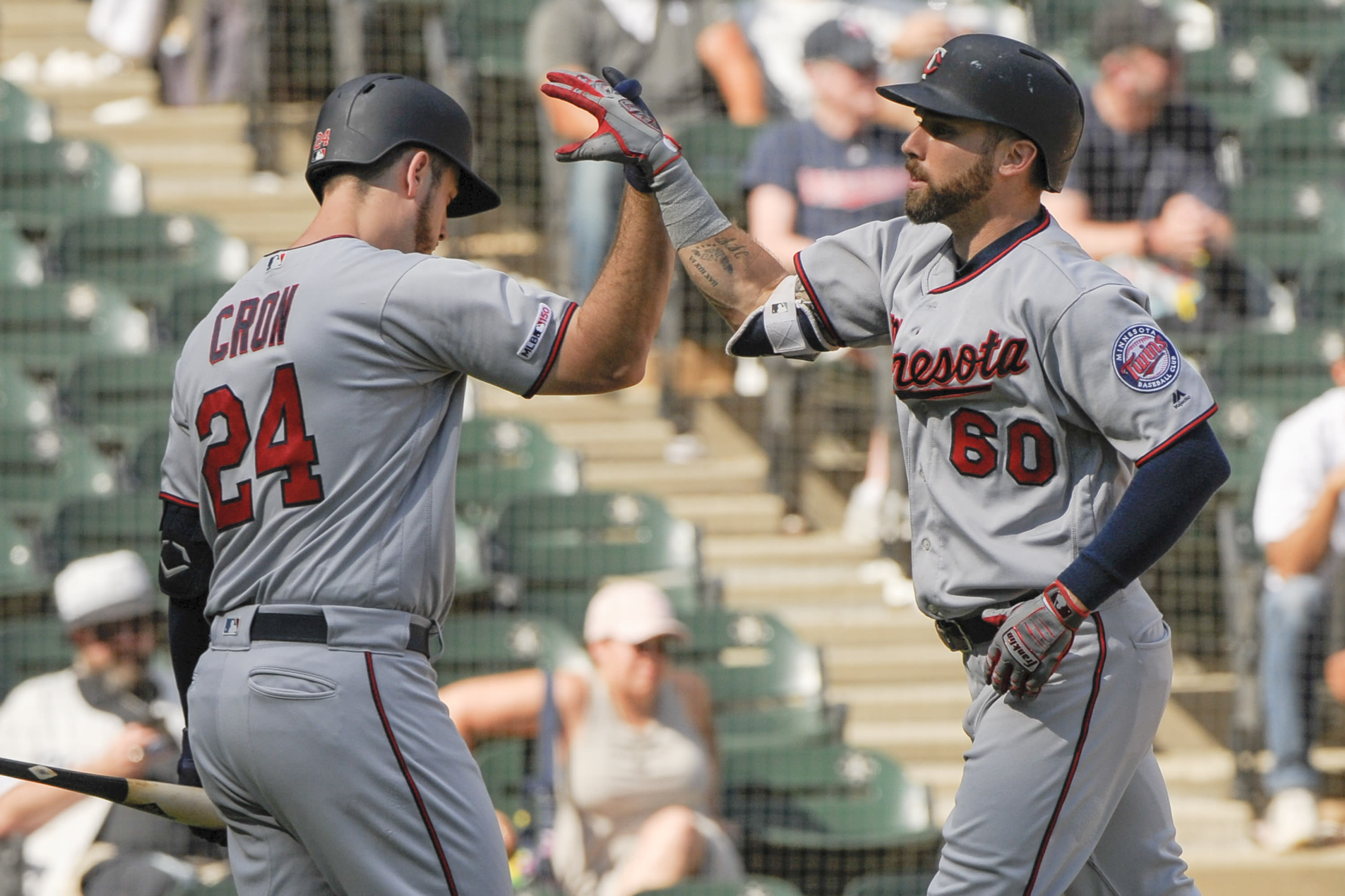 Minnesota Twins' C.J. Cron (24) congratulates Jake Cave (60) on his seventh-inning home run against the Chicago White Sox during a baseball game Thursday, Aug. 29, 2019, in Chicago. (AP Photo/Mark Black)