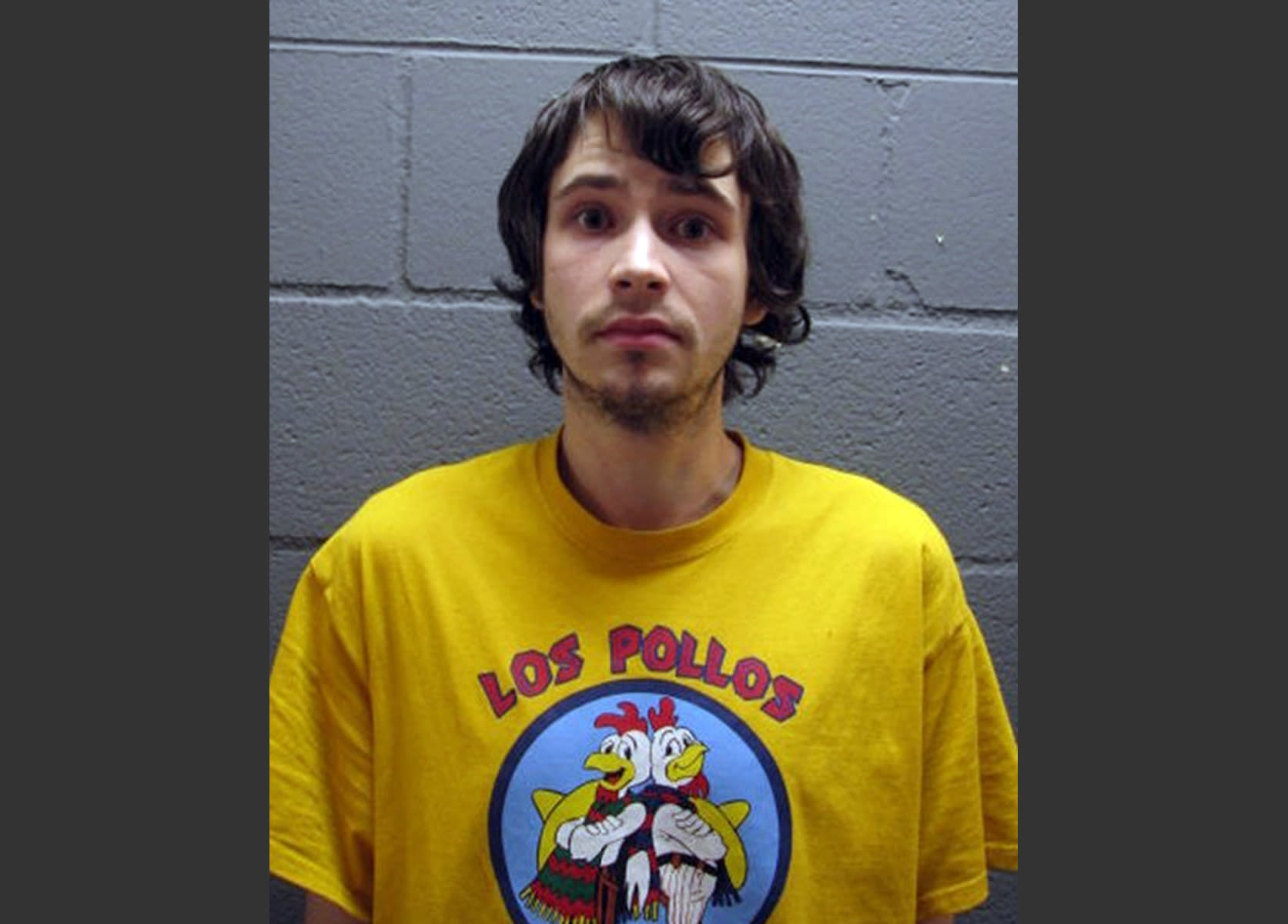 """In this undated booking photo provided by the Cook County Sheriff's Office, Daniel Kowalski, a suburban Chicago man accused of operating a methamphetamine lab, wears a t-shirt for the fictional Los Pollos Hermanos chicken restaurant depicted in """"Breaking Bad,"""" a show about a methamphetamine manufacturer. Kowalski, 21, is charged with felony possession of a controlled substance, methamphetamine manufacturing materials and precursors. (AP Photo/Cook County Sheriff's Office)"""