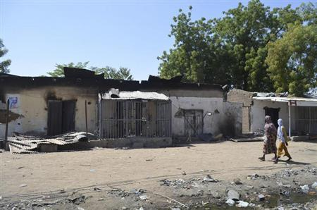 Women walk by homes destroyed by Boko Haram militants in Bama