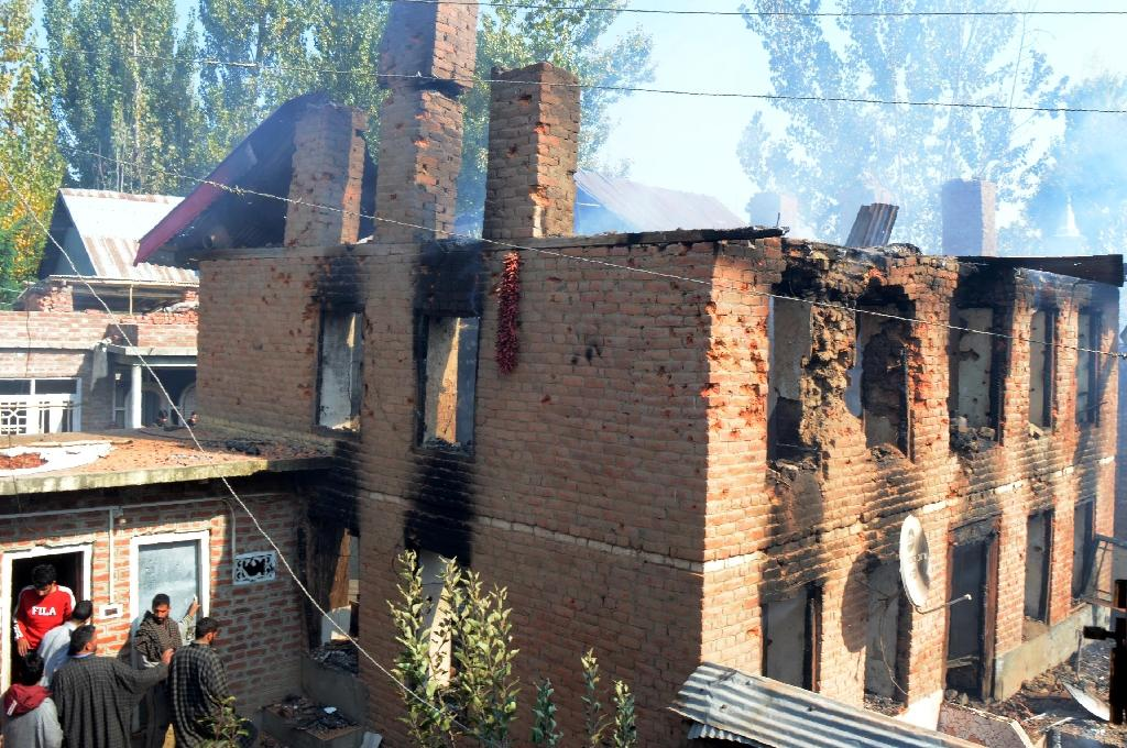 Indian Kashmiri residents look on as smoke billows from a house after a gunfight with Indian government forces in Kulgam town, some 65 kms south of Srinagar on October 21, 2018