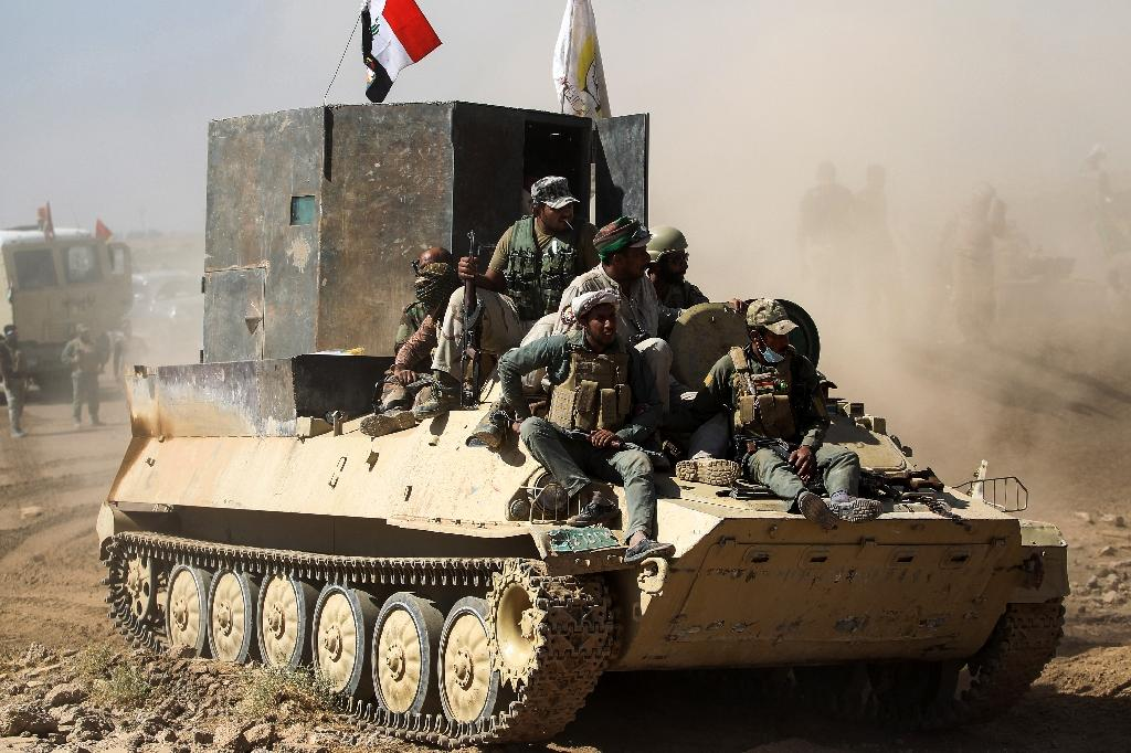 Fighters from Iraq's Hashed al-Shaabi paramilitary coalition ride on an infantry-fighting vehicle during an advance against the Islamic State group on October 6, 2017