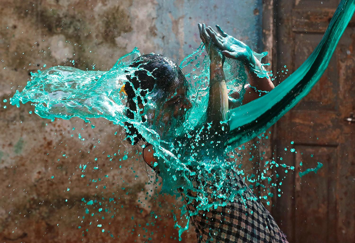 <p>A girl reacts as colored water is thrown on her face while celebrating Holi, the Festival of Colors, in Mumbai, India, March 13, 2017. (Shailesh Andrade/Reuters) </p>