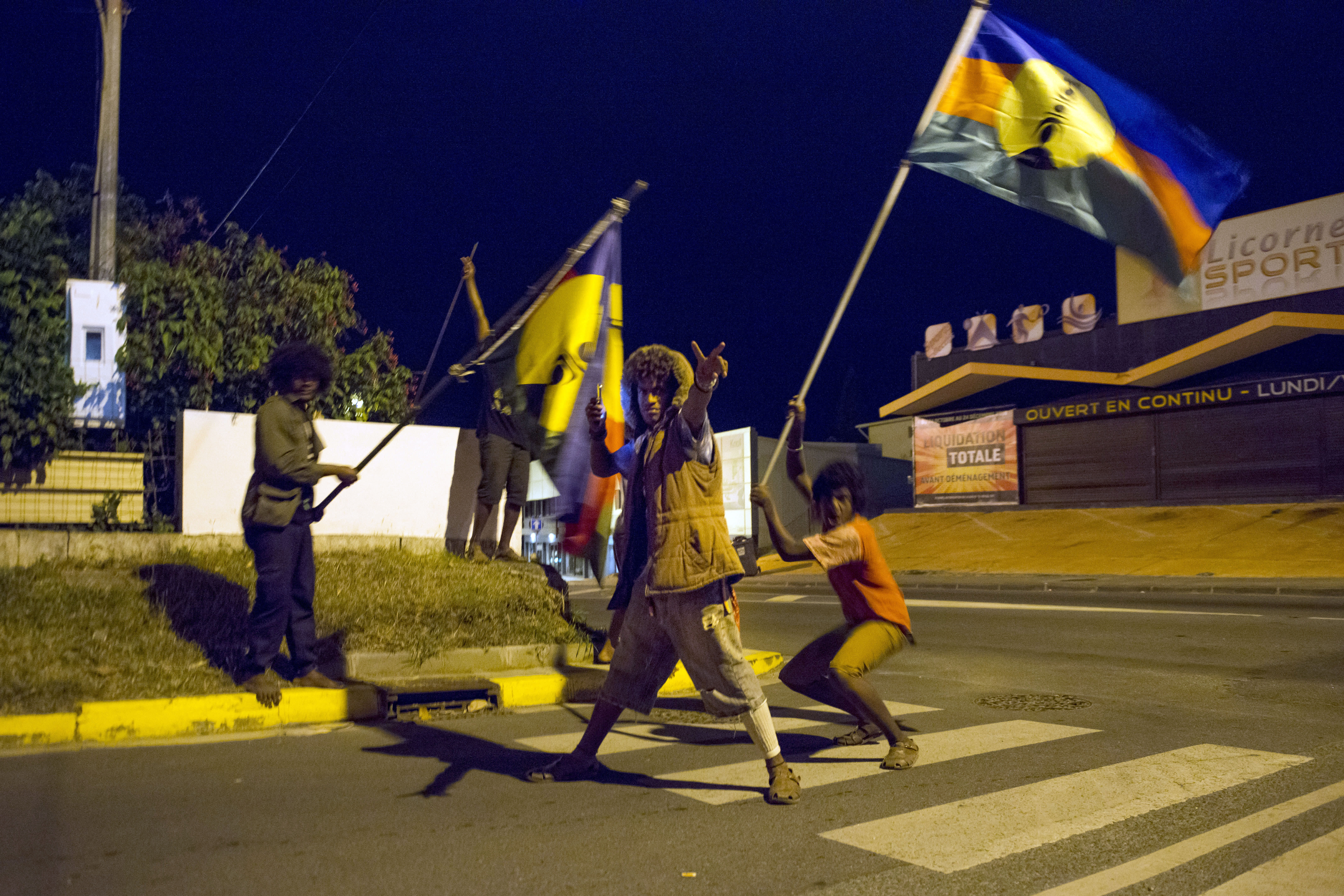 FILE - In this Nov.4, 2018 file photo, pro-independence activist strike a pose as they celebrate in the streets of Noumea, the New Caledonia's capital, while waving the indigenous Malanesian flag called the 'Kanak' flag. Voters in New Caledonia, a French archipelago in the South Pacific, are to choose whether they want independence from France in a referendum that marks a milestone in a three-decades-long decolonization effort. The vote on Sunday, Oct. 4, 2020 is key to determine the future of the archipelago east of Australia and its 270,000 inhabitants, including the native Kanaks, who once suffered from strict segregation policies, and the descendants of European colonizers. (AP Photo/Mathurin Derel, file)