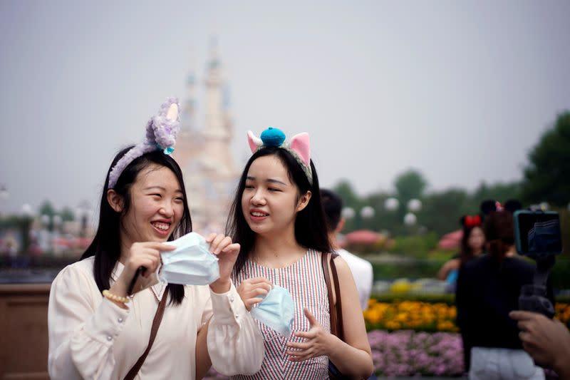 FILE PHOTO: Visitors hold face masks at the Shanghai Disneyland
