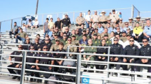 Dozens of police officers cheer on teen at his first football game after he lost his dad in the line of duty