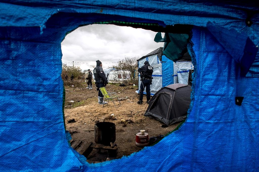 "A photo taken through a hole in a sheet of blue tarp shows French riot police officers surveying the southern half of the ""Jungle"" migrant camp in the French port city of Calais on March 4, 2016 (AFP Photo/Philippe Huguen)"