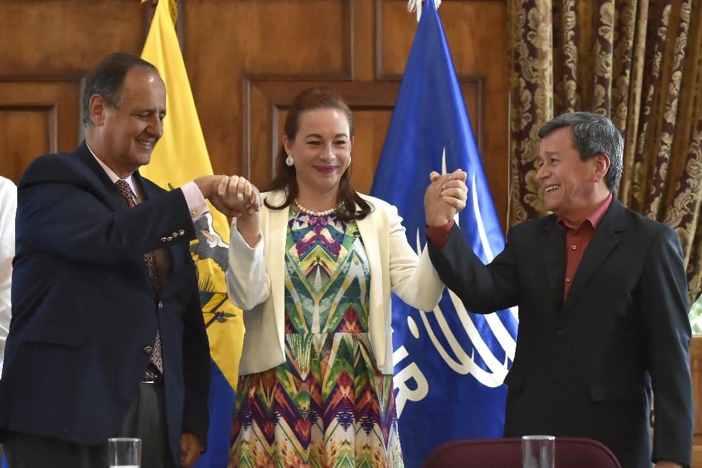 Ecuadoran Foreign Minister Maria Fernanda Espinoza, center, raises the hands of chief negotiators Juan Camilo Restrepo, left for the Colombian government, and Pablo Beltran, for the ELN guerrillas in Quito on September 4, 2017 (AFP Photo/RODRIGO BUENDIA)