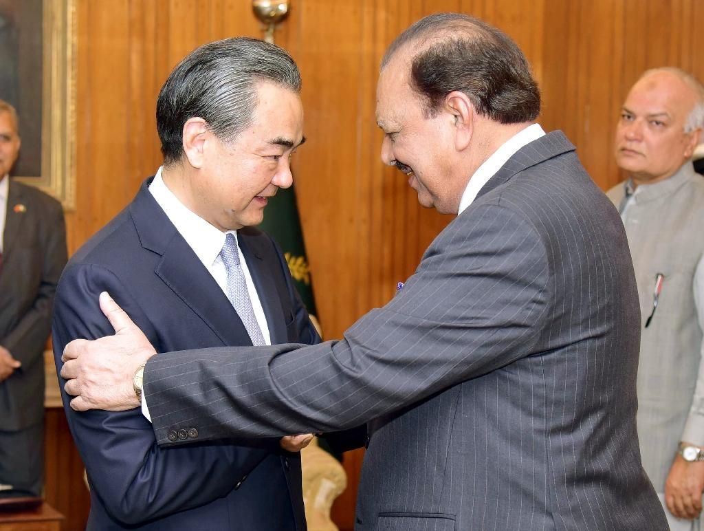 Pakistani President Mamnoon Hussain (R) shakes hands with Chinese Foreign Minister Wang Yi upon his arrival in Islamabad
