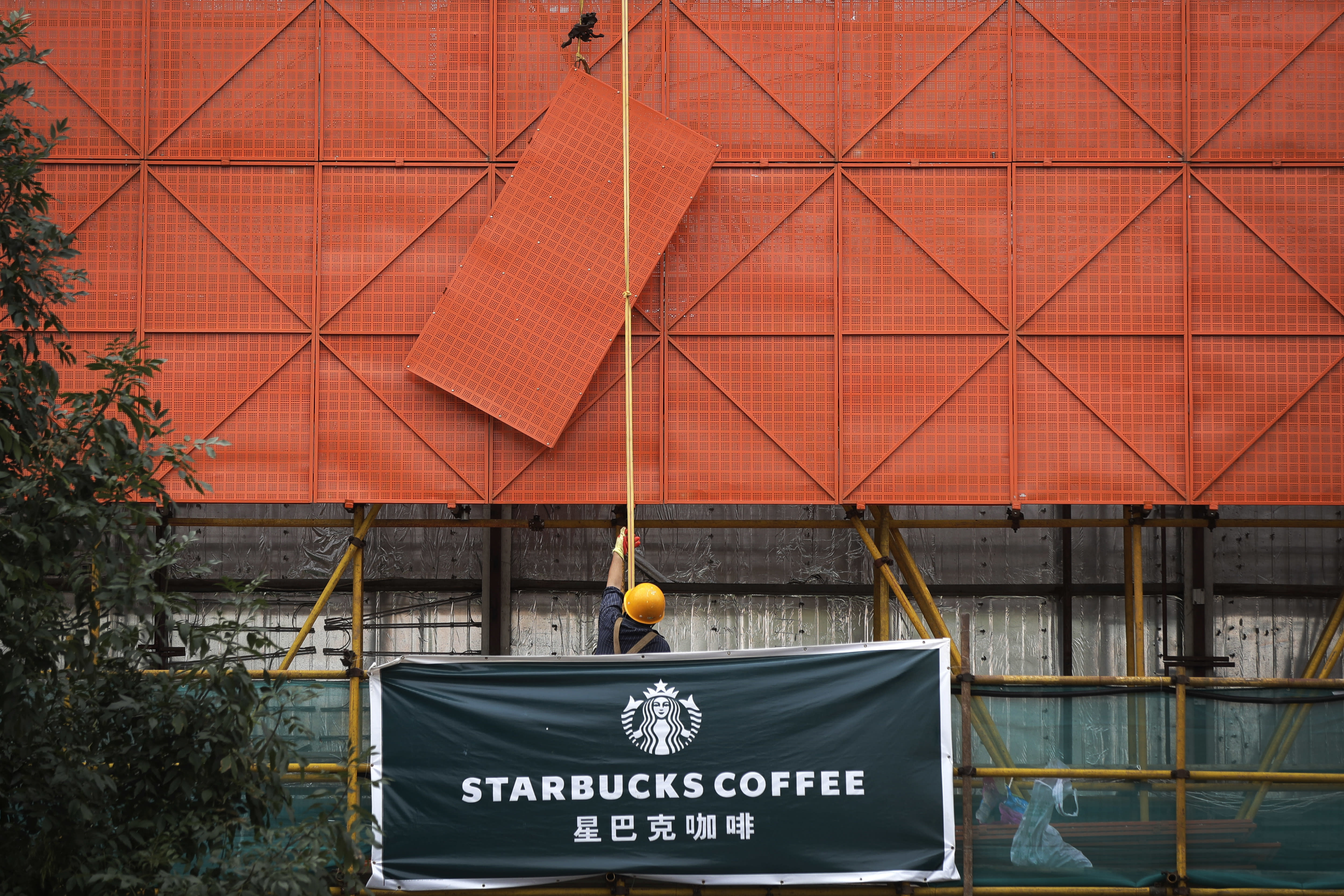 FILE - In an Aug. 14, 2018 file photo, a worker lifts a protection steel frame on a Starbucks cafe banner hanging outside a shopping mall under renovation in Beijing. A report out Monday, May 11, 2020, found that China's direct investment in the United States dropped from $5.4 billion in 2018 to $5 billion last year, the lowest level since the recession year of 2009. (AP Photo/Andy Wong, File)