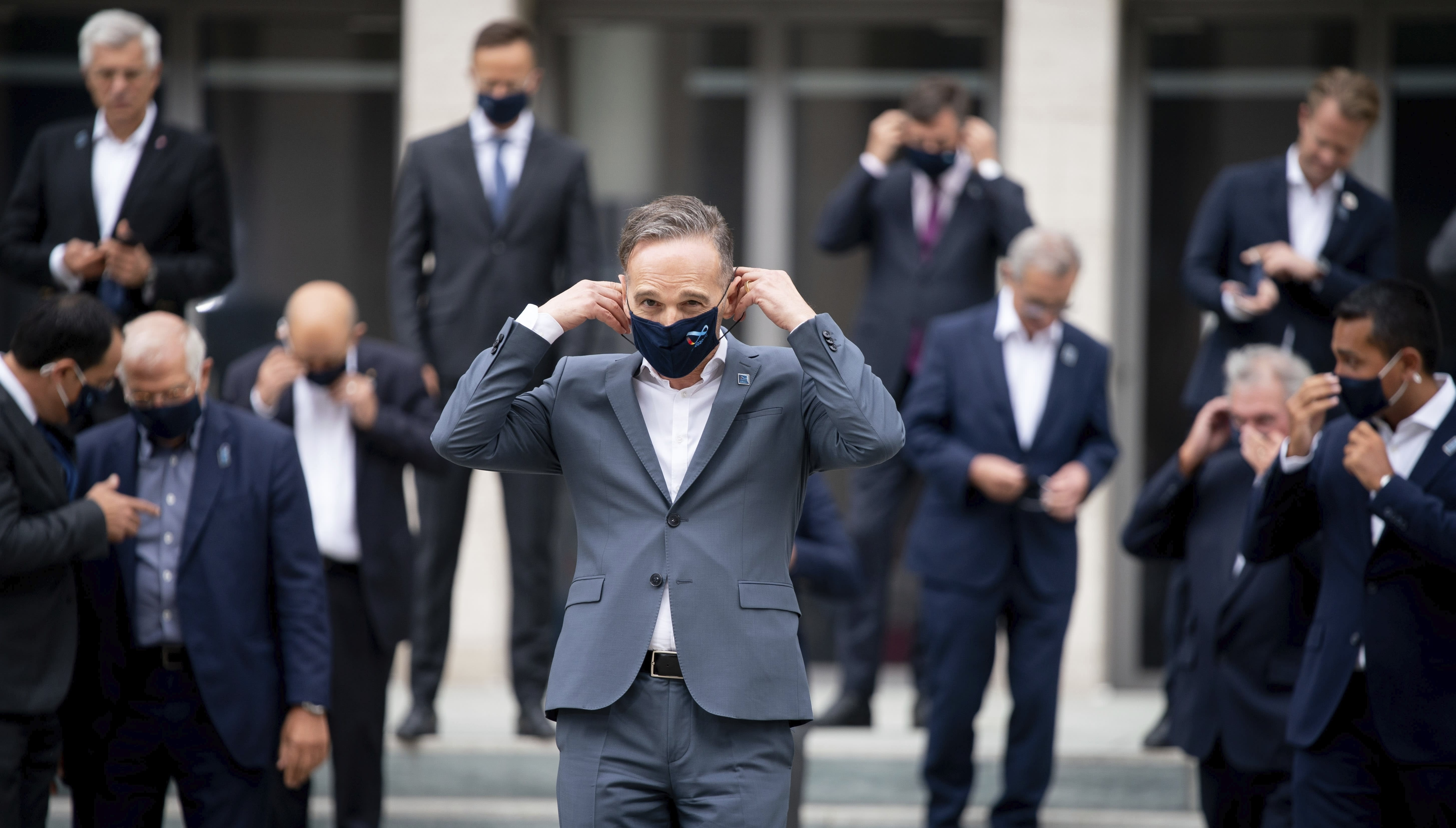 Foreign Minister Heiko Maas, wearing a mouth-and-nose protector, meets his EU counterparts for the family photo on the fringes of the informal talks between the EU Foreign Ministers and their EU counterparts. The topics of the so-called Gymnich meeting include developments in Belarus and the dispute over natural gas in the eastern Mediterranean between Turkey and the EU states of Greece and Cyprus. (Kay Nietfeld/dpa via AP)