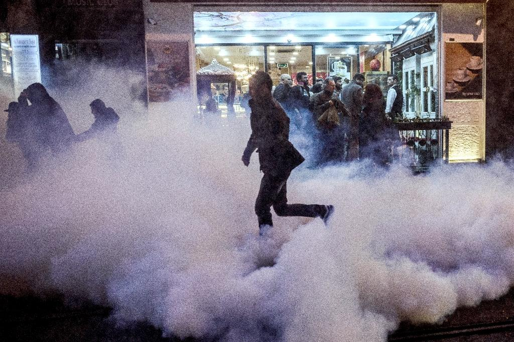 A protester runs for cover from tear gas fired by Turkish riot police to disperse protesters during a demonstration after a top Kurdish lawyer was killed in Diyarbakir on November 28, 2015 (AFP Photo/Ozan Kose )