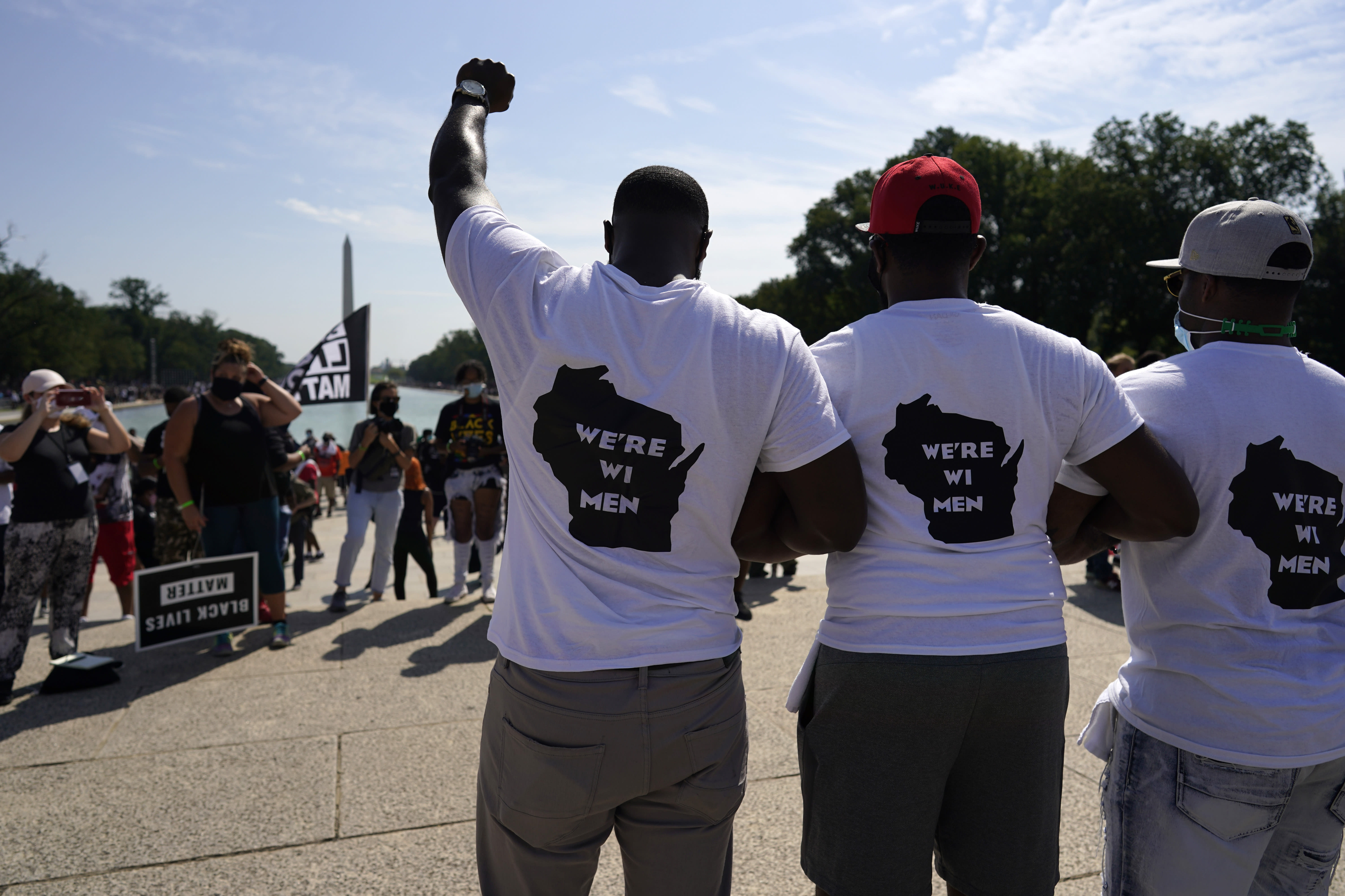 """Men from Milwaukee wear """"We're WI Men"""" T-shirts as they attend the March on Washington, Friday Aug. 28, 2020, in Washington, on the 57th anniversary of the Rev. Martin Luther King Jr.'s """"I Have A Dream"""" speech. (AP Photo/Carolyn Kaster)"""