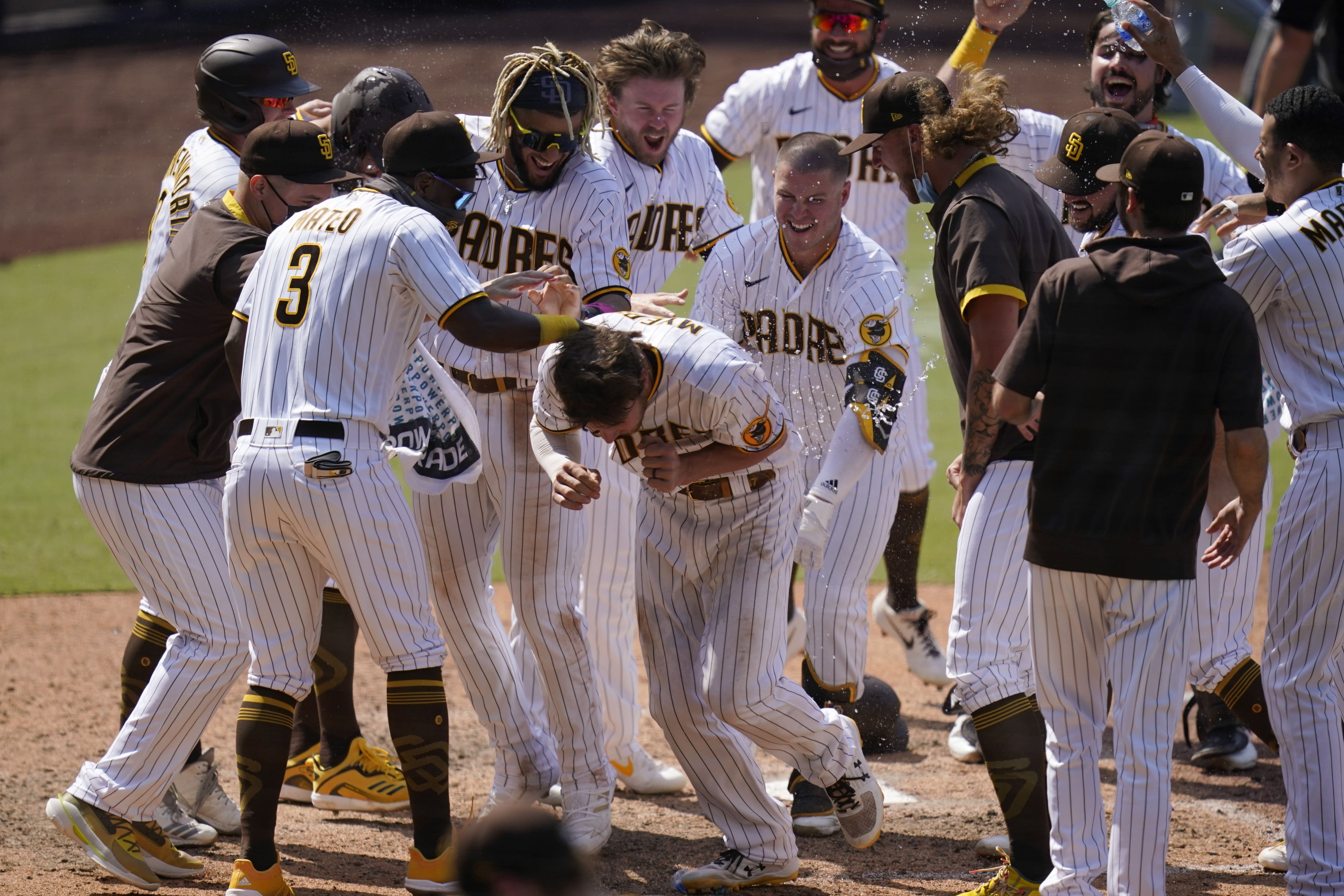 San Diego Padres' Wil Myers, center, reacts with teammates after hitting a three-run walkoff home run to defeat the Seattle Mariners in a baseball game Thursday, Aug. 27, 2020, in San Diego. (AP Photo/Gregory Bull)