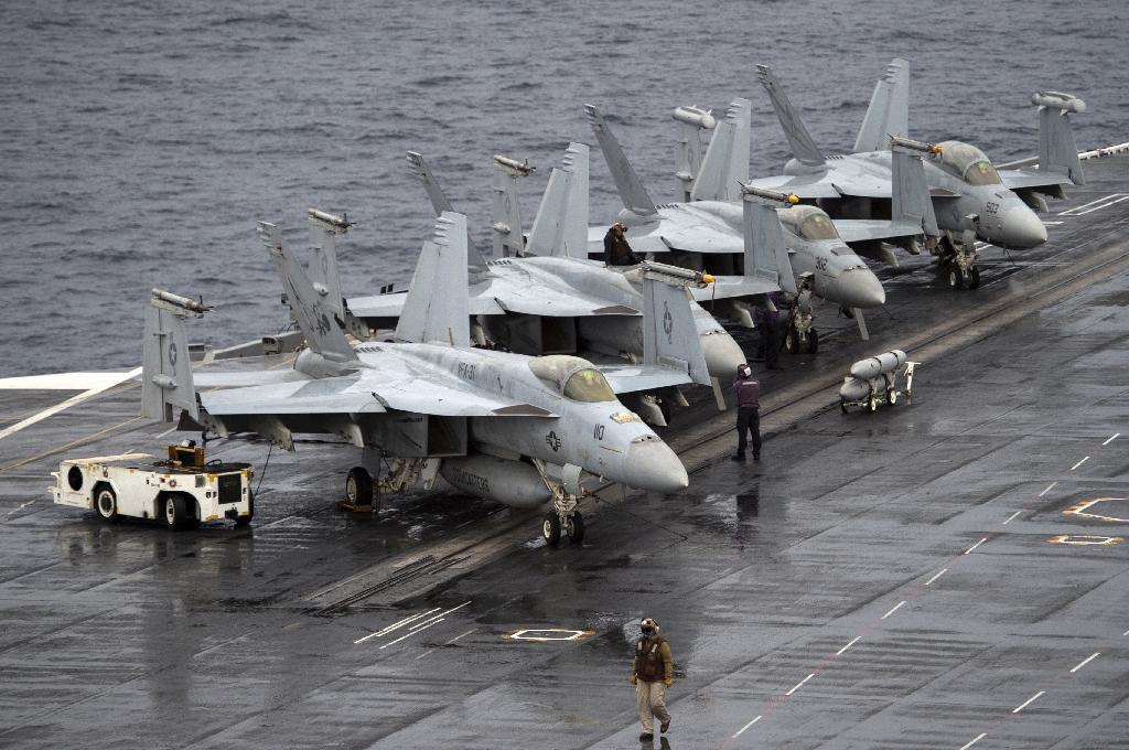 Warplanes are parked on the deck of the Norfolk-based USS George H.W. Bush aircraft carrier in the Atlantic Ocean during war games in October 2017