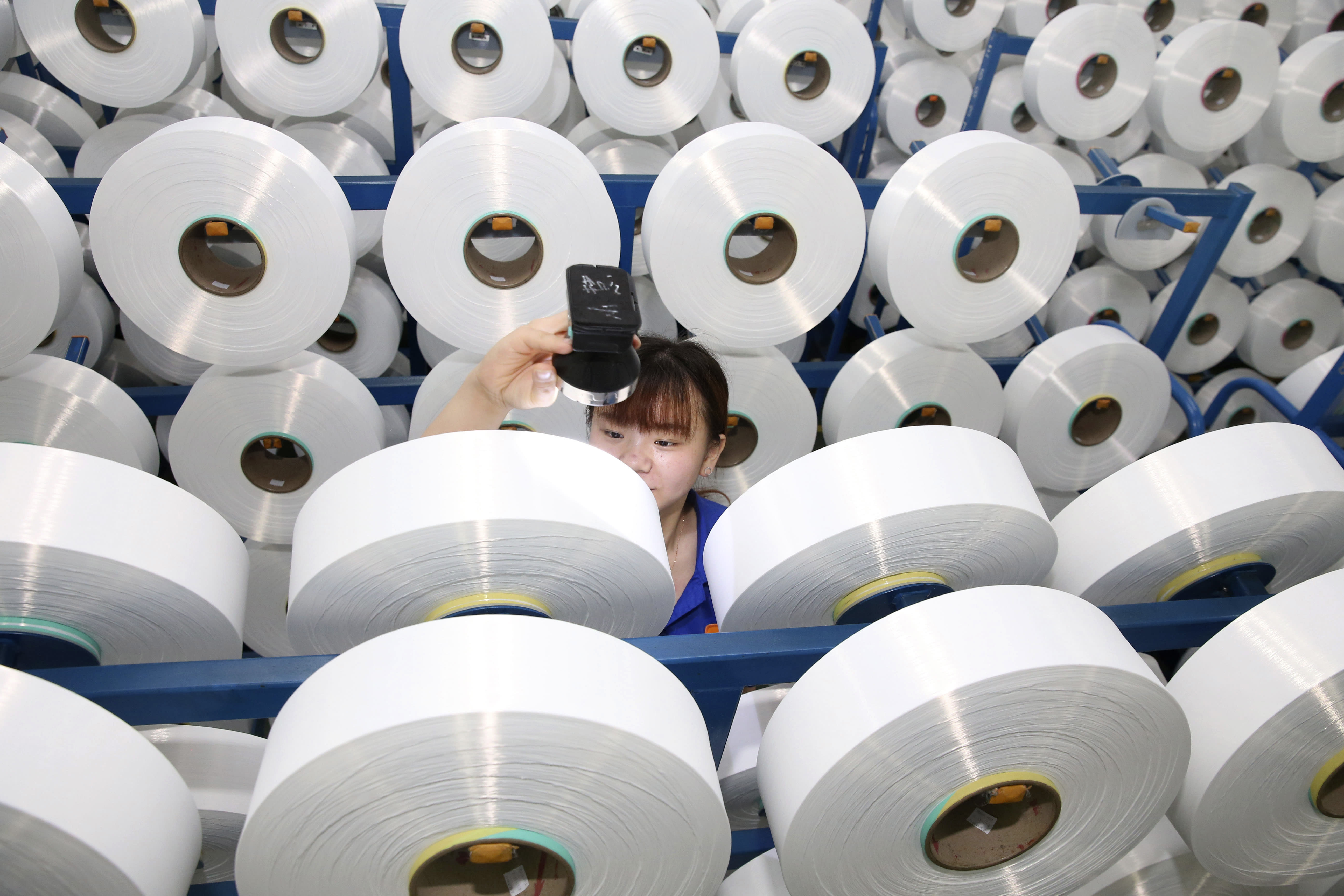 In this Aug. 25, 2019, photo, an employee works on the production line of a polyester manufacturer in Suzhou in eastern China's Jiangsu province. Two surveys of Chinese manufacturing show demand is weak amid a mounting tariff war with Washington over trade and technology. (Chinatopix via AP)