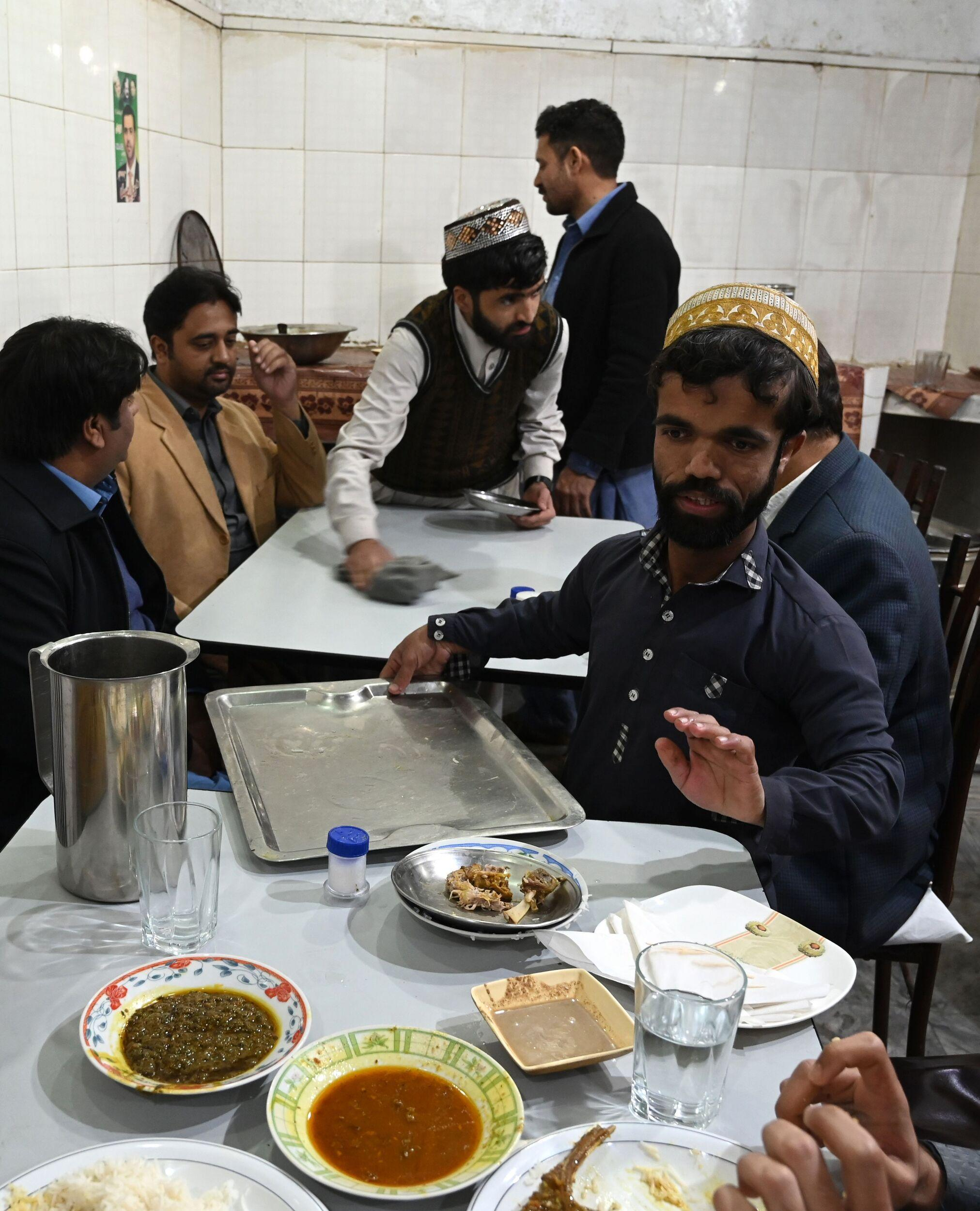 In this picture taken on February 22, 2019, Rozi Khan (R), a 25-year-old Pakistani waiter who resembles US actor Peter Dinklage, serves food to customers at Dilbar Hotel in Rawalpindi. - Rozi Khan had never heard of the Game of Thrones -- or its hugely popular character Tyrion Lannister -- until his striking resemblance to the dwarf anti-hero got heads turning at home. (Photo by AAMIR QURESHI / AFP) / To go with PAKISTAN-LIFESTYLE-TELEVISION-ENTERTAINMENT        (Photo credit should read AAMIR QURESHI/AFP/Getty Images)