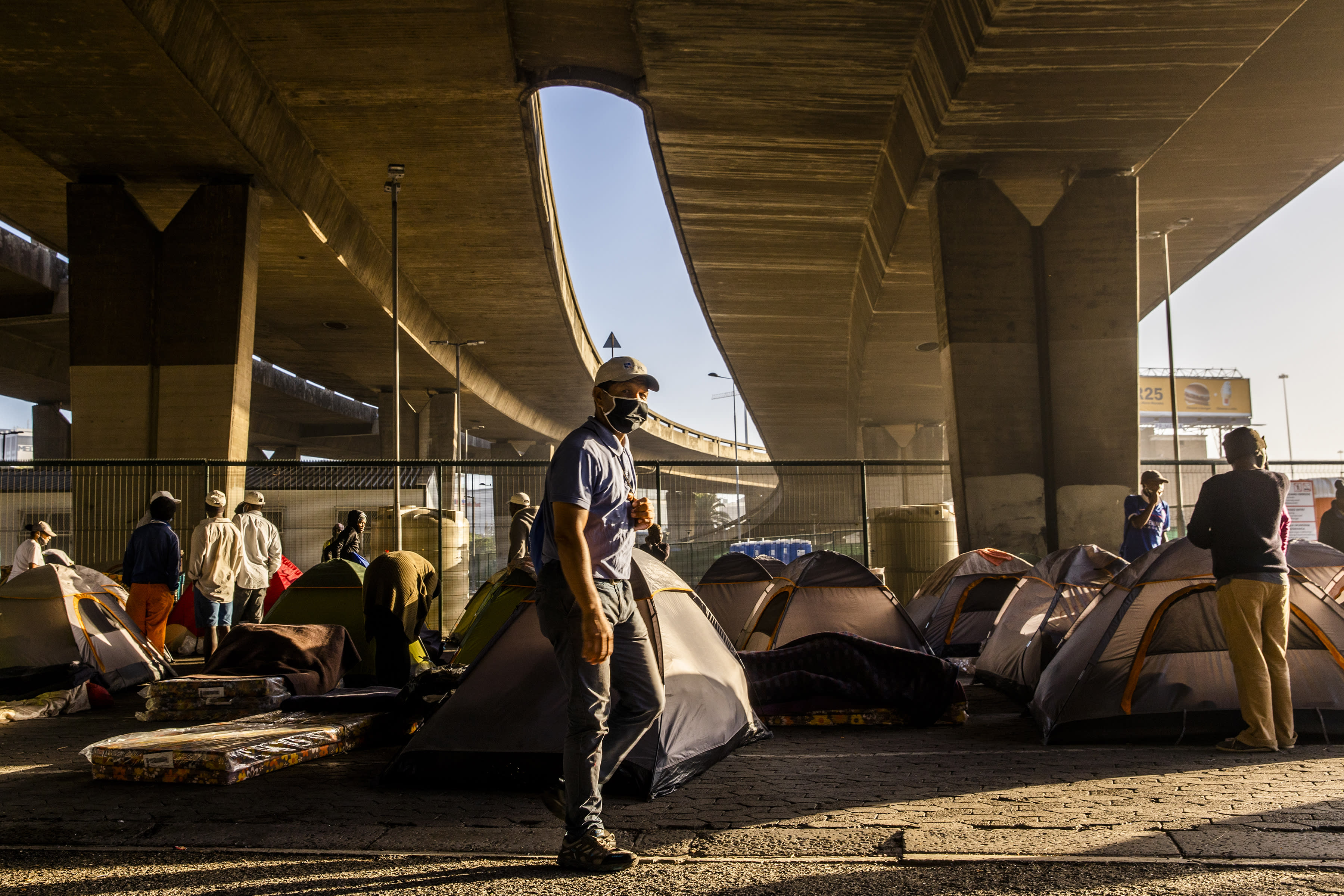 Homeless people living in tents under a bridge in Cape Town, South Africa, Friday, May 22, 2020, after being transported from a closed shelter to another unfinished shelter. (AP Photo)