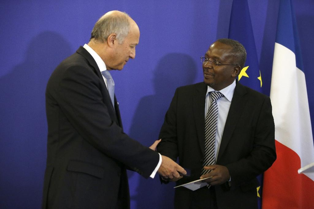 Burundian journalist Esdras Ndikumana (R) receives the diplomatic press award from French Foreign Minister Laurent Fabius, on January 11, 2016 in Paris