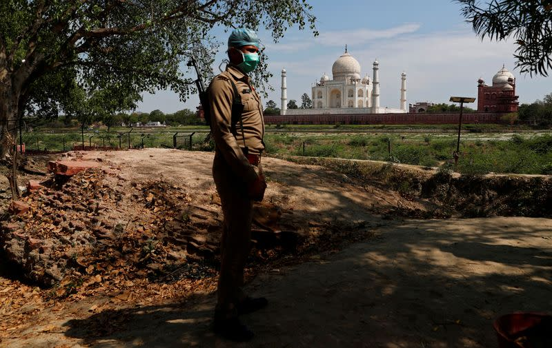 FILE PHOTO: A policeman wearing a protective mask stands guard near the historic Taj Mahal during a nationwide lockdown