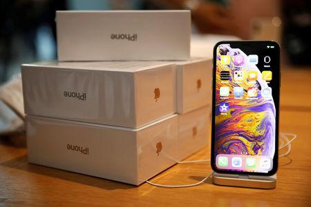 45e5a1e20af Boxes of iPhones purchased by customers are pictured next to an iPhone XS  on display at