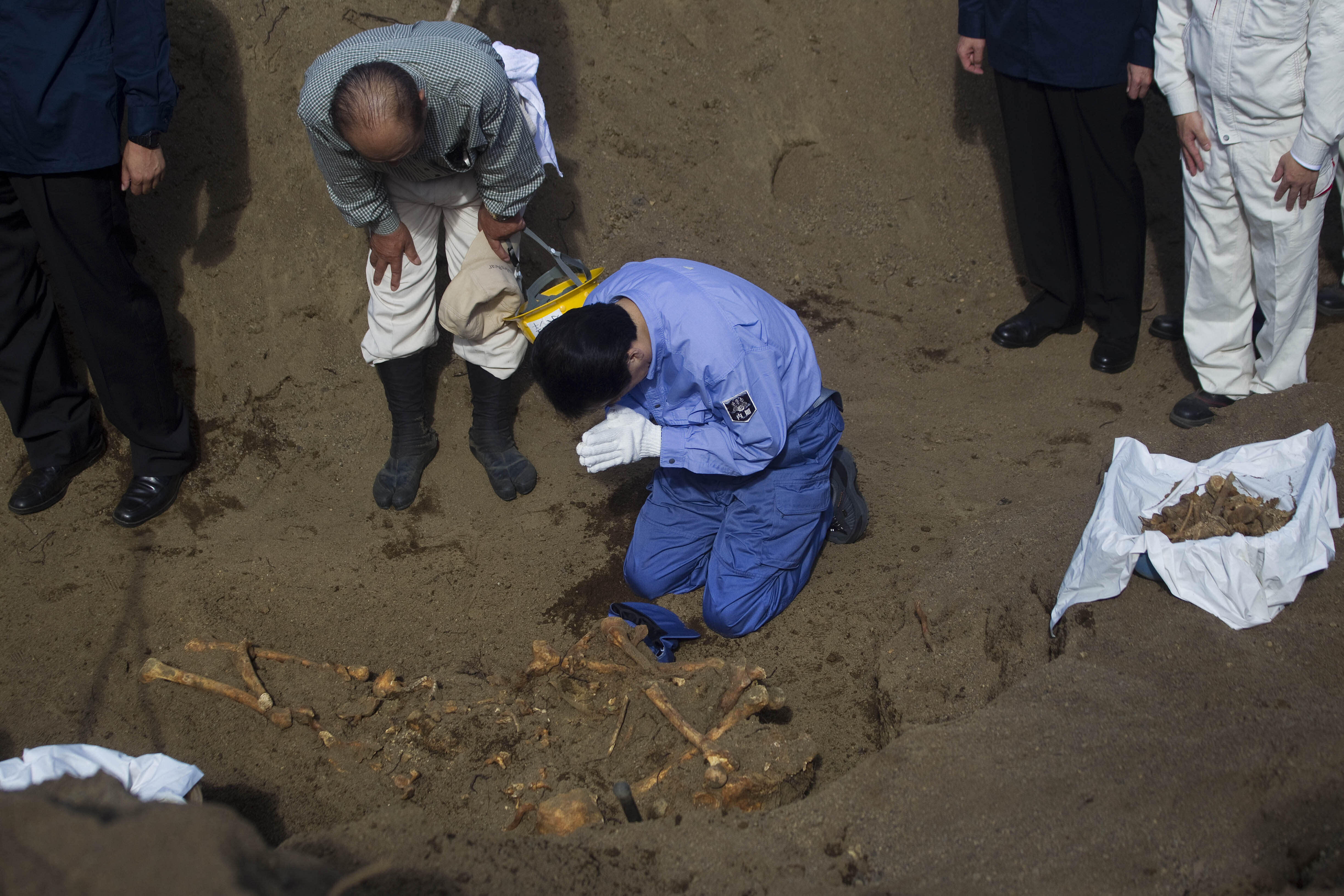 FILE - In this Dec. 14, 2010, file photo, then Japanese Prime Minister Naoto Kan bows at a mass grave site on Iwo Jima island where officials discovered the remains of Japanese soldiers who died in the battle for Iwo Jima. Seventy-five years after the end of World War II, more than 1 million Japanese war dead are scattered throughout Asia, where the legacy of Japanese aggression still hampers recovery efforts. The missing Japanese make up about half of the 2.4 million soldiers who died overseas during Japan's military rampage across Asia in the early 20th century.(AP Photo/David Guttenfelder, File)