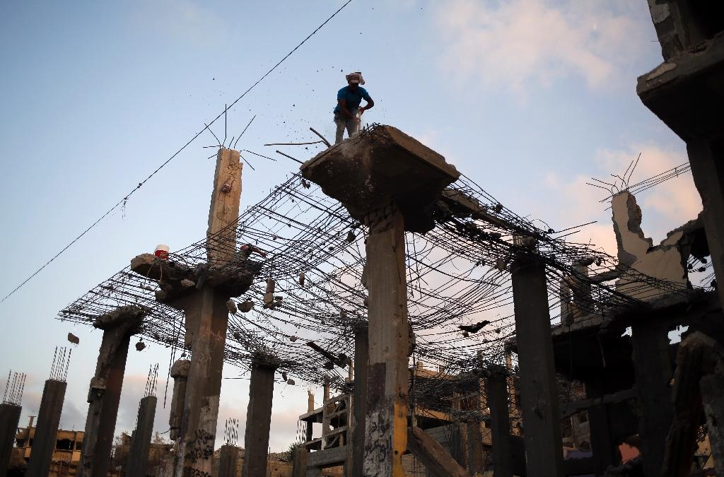 Palestinian workers remove the rubble of a building that was destroyed during the 50-day war between Israel and Hamas militants in the summer of 2014, on August 23, 2015 in Gaza City's eastern suburb of Al-Shejaiya (AFP Photo/Mohammed Abed)