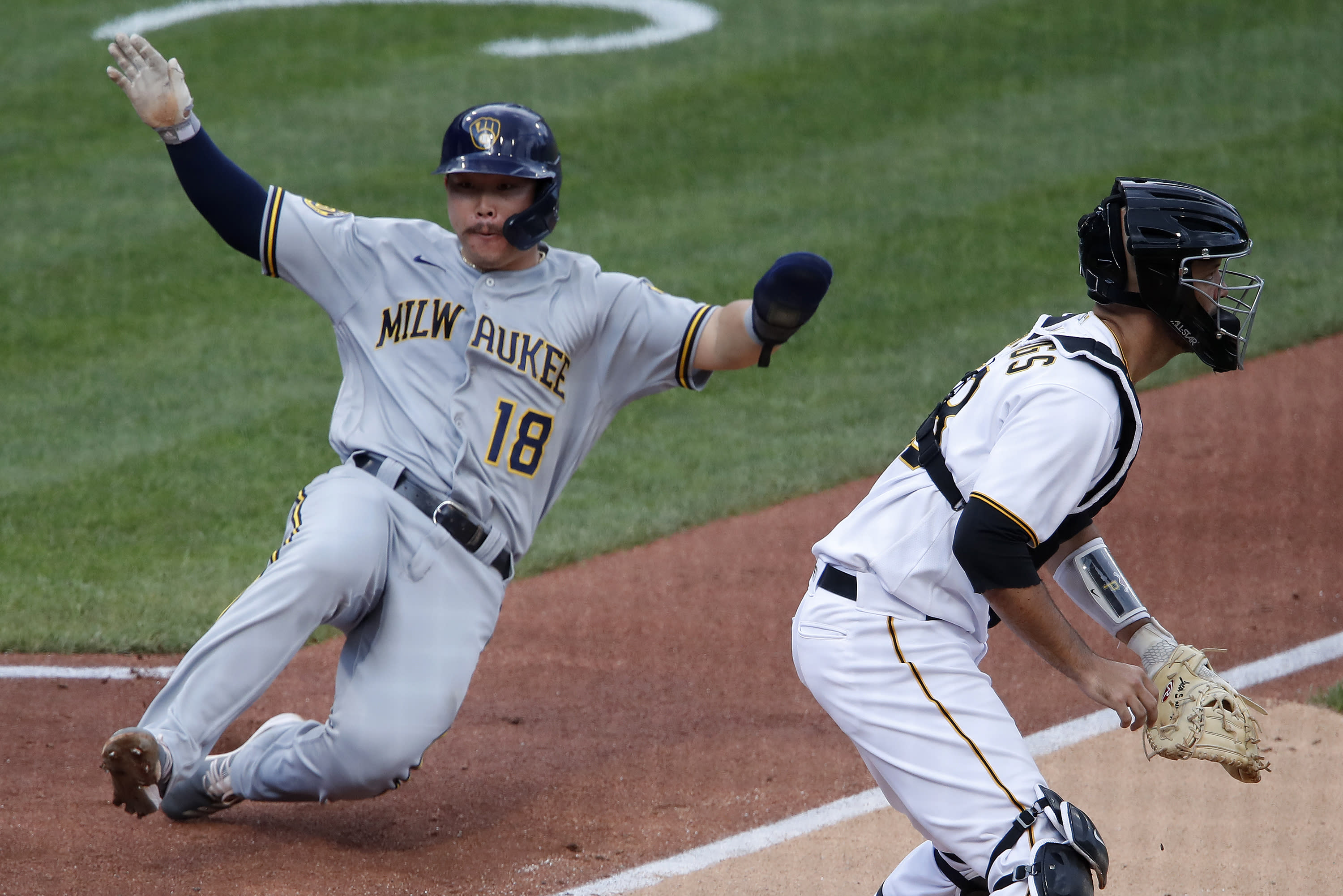 Milwaukee Brewers' Keston Hiura (18) scores on a double by Justin Smoak as Pittsburgh Pirates catcher Jacob Stallings waits for the late relay during the fourth inning of a baseball game in Pittsburgh, Sunday, Aug. 23, 2020. (AP Photo/Gene J. Puskar)