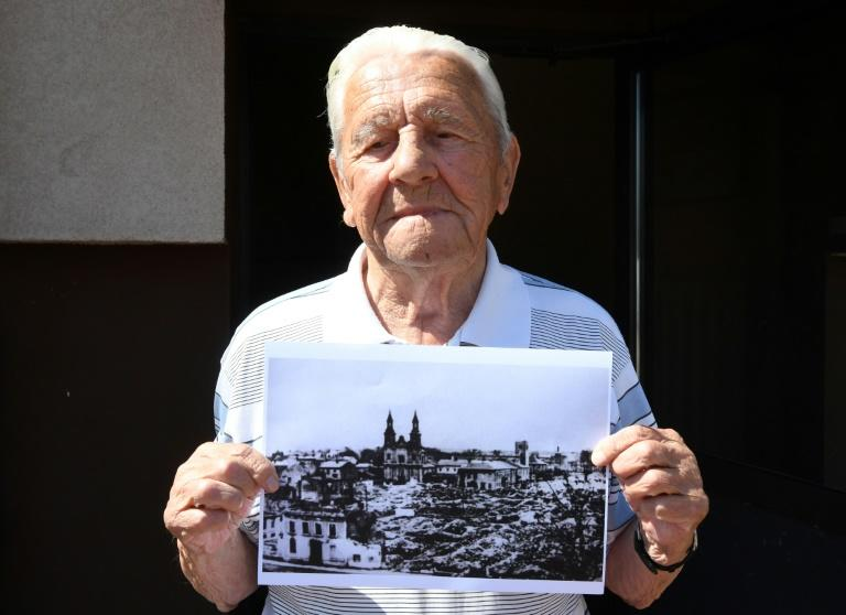 Tadeusz Sierandt, an eyewitness to the bombing of Wielun, holds a picture of the destroyed town (AFP Photo/Janek SKARZYNSKI)