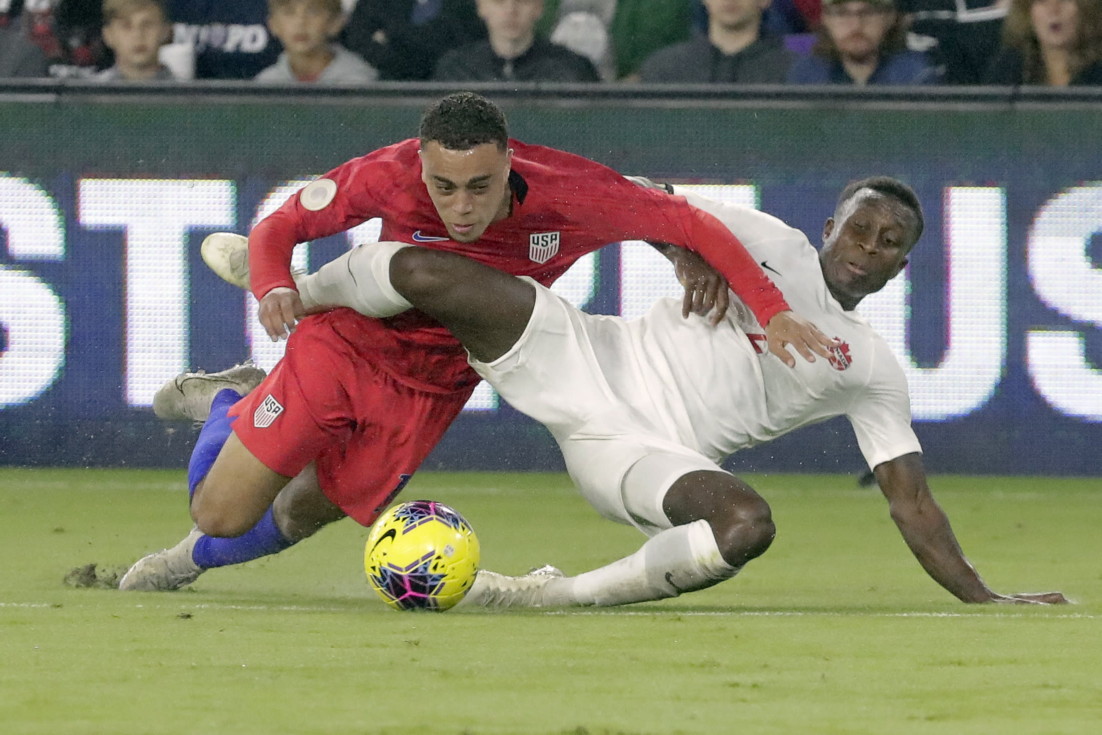 U.S. defender Sergino Dest, left, gets tangled up with Canada defender Richie Laryea while going after the ball during the first half of a CONCACAF Nations League soccer match Friday, Nov. 15, 2019, in Orlando, Fla. (AP Photo/John Raoux)