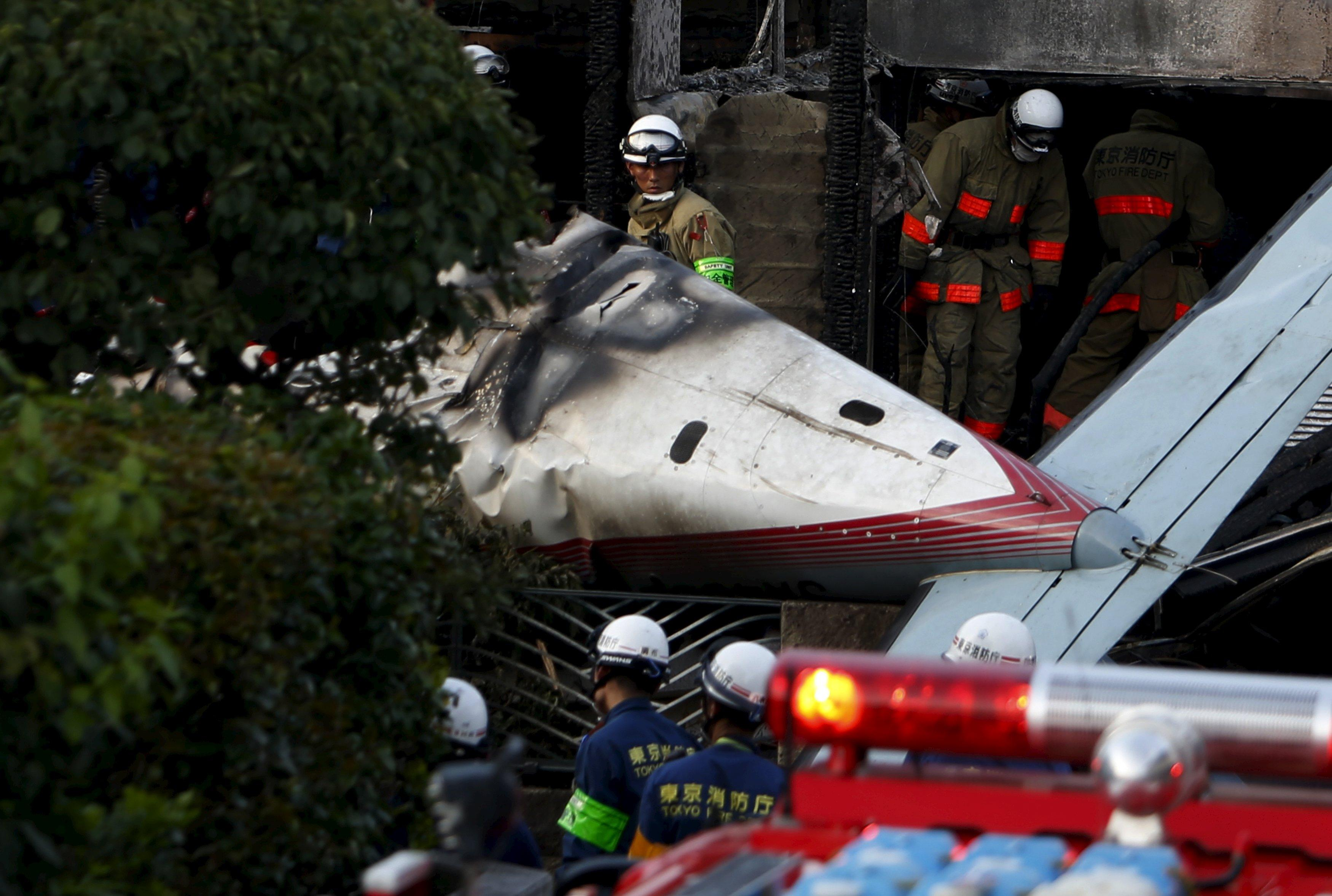 A firefighter looks at the tail section of a small airplane as he removes wreckage and debris at the site where the light plane went down in a residential area and burst into flames, in Chofu, outskirt of Tokyo, July 26, 2015. Three people were killed when a small airplane crashed into a residential area of the Japanese capital, Tokyo, on Sunday, public broadcaster NHK reported, setting fire to houses and cars. REUTERS/Yuya Shino