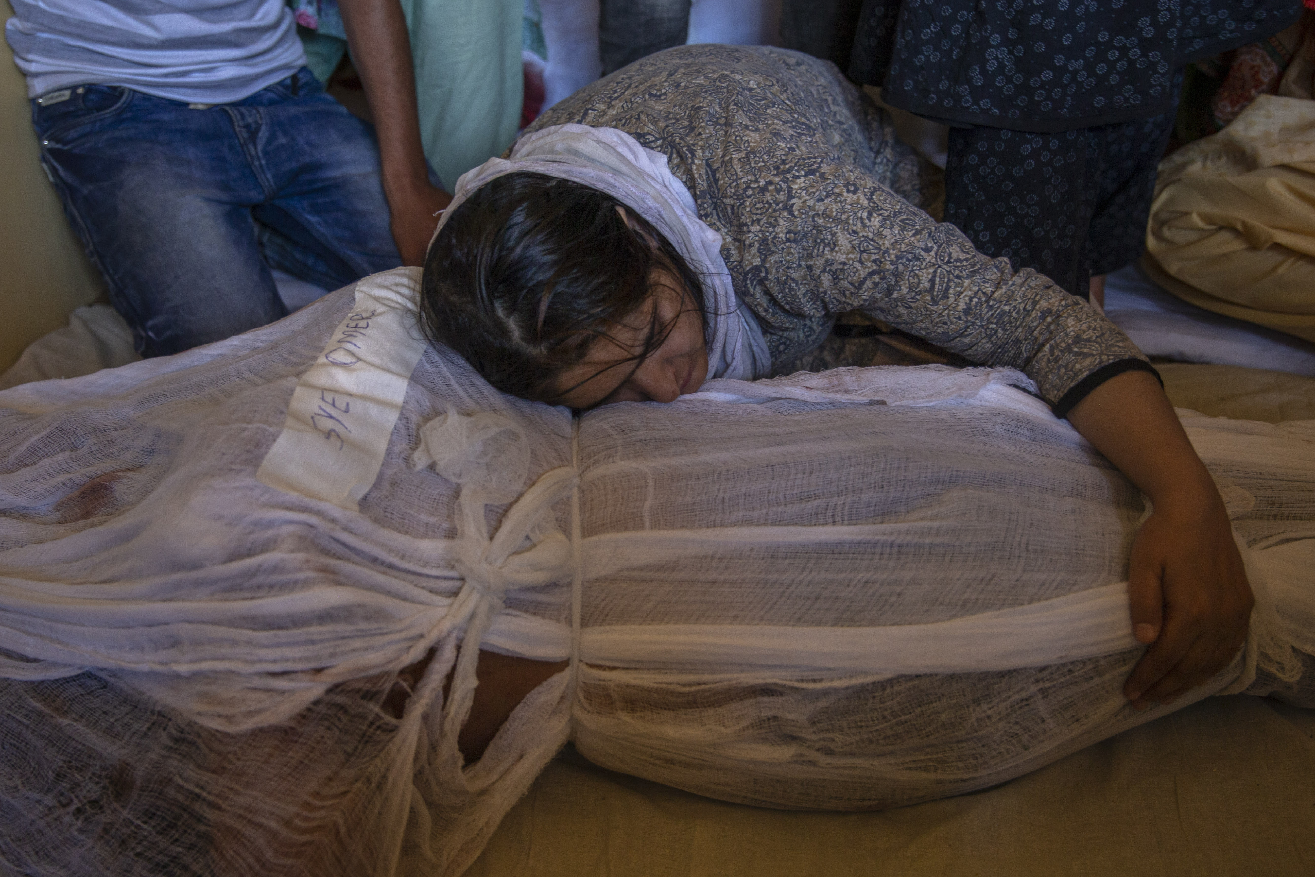 A girl mourns by the body of her brother Syed Omer Bari in Bandipora town, north of Srinagar, Indian controlled Kashmir, Thursday, July 9, 2020. Unidentified assailants late Wednesday fatally shot Sheikh Wasim Bari, a leader with Prime Minister Narendra Modi's Bharatiya Janata Party, along with his father and brother Syed Omer Bari in Kashmir, police said, in a first major attack against India's ruling party members in the disputed region. (AP Photo/ Dar Yasin)