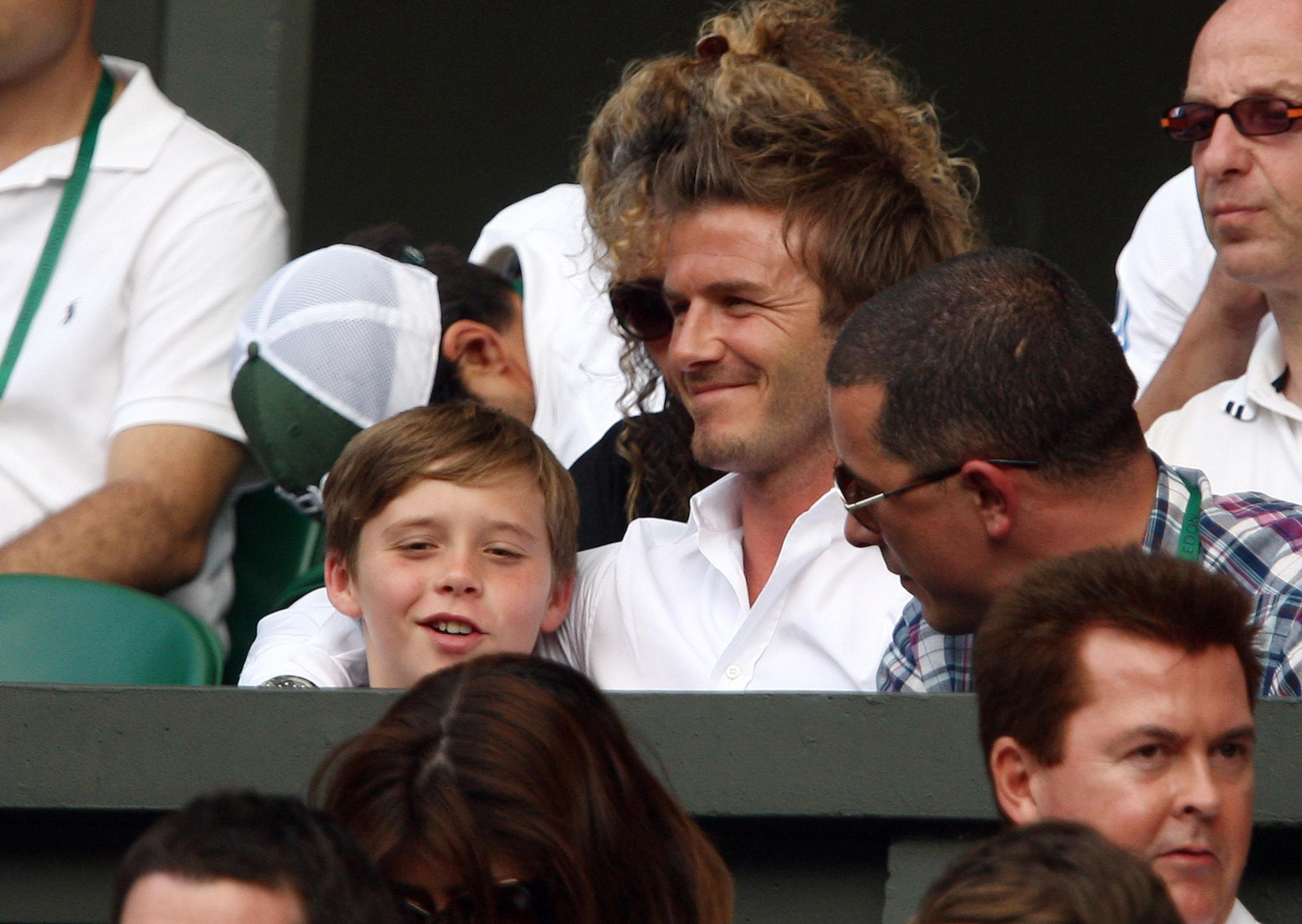 Tennis - Wimbledon - All England Lawn Tennis & Croquet Club, Wimbledon, England - 2/7/10  David Beckham (C) and son Brooklyn (L) in the stands during Great Britain's Andy Murray  semi final match  Mandatory Credit: Action Images / Paul Childs  Livepic