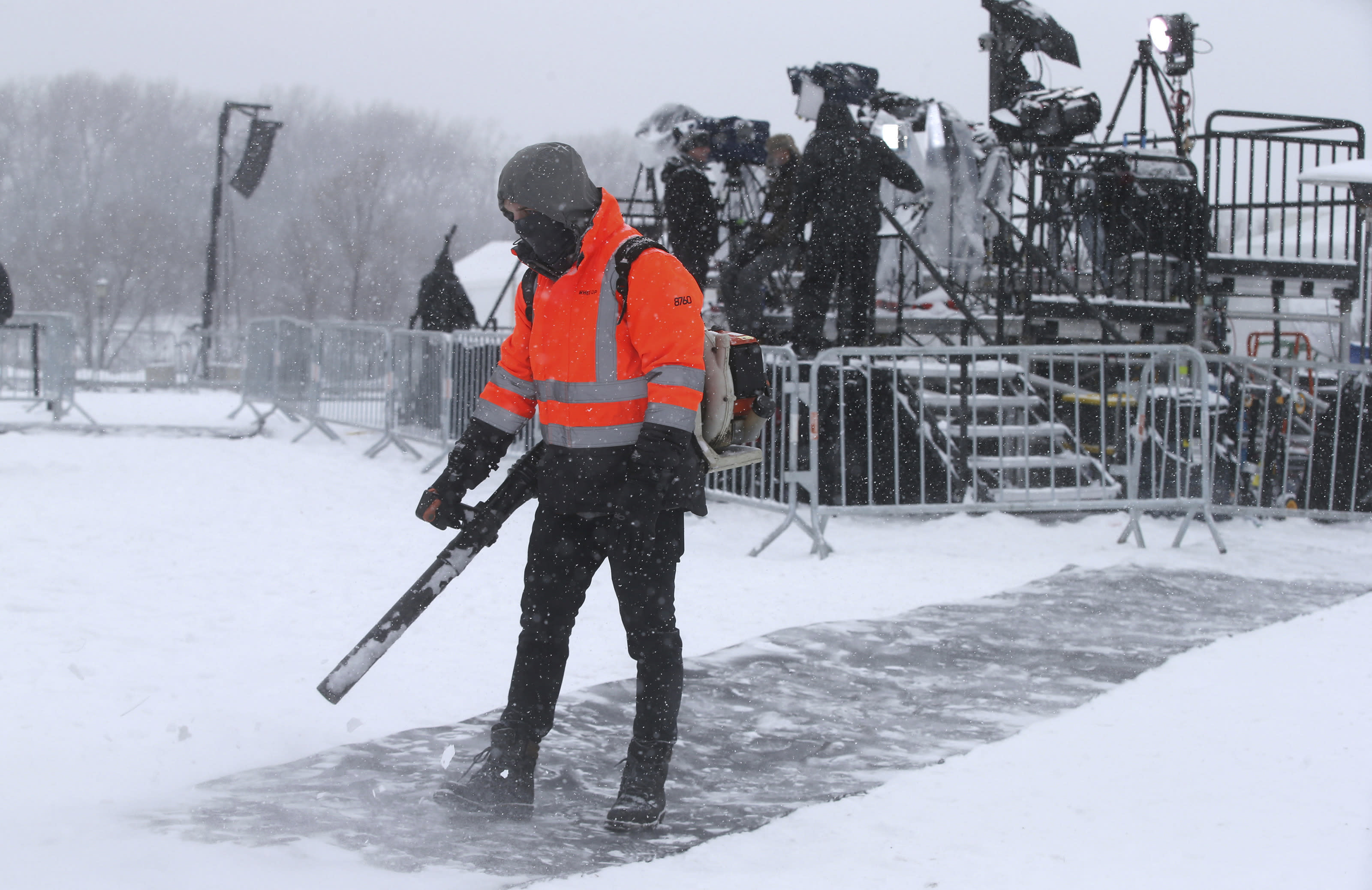 Snow continues to fall as a worker clears snow off a runner and media members arrange equipment on a riser prior to Democratic Sen. Amy Klobuchar's announcement of her decision in the race for president at a rally Sunday, Feb. 10, 2019, at Boom Island Park in Minneapolis. (AP Photo/Jim Mone)