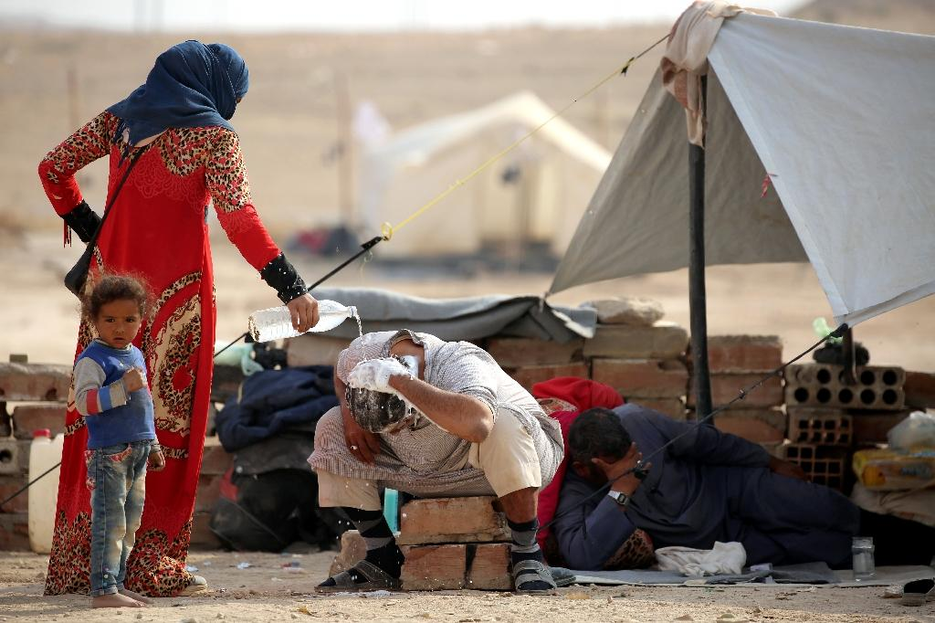 An Iraqi refugee who fled Mosul helps a man wash his hair at the UN-run Al-Hol refugee camp in Syria's Hasakeh province, on October 25, 2016 (AFP Photo/Delil Souleiman)