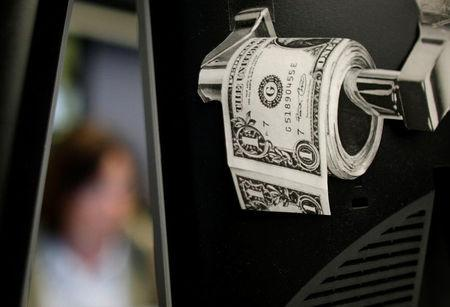 FILE PHOTO: A magazine cut-out of a toilet roll made up of paper money, is taped to a screen of a trading terminal at the German stock exchange in Frankfurt, June 3, 2009. REUTERS/Kai Pfaffenbach/File Photo