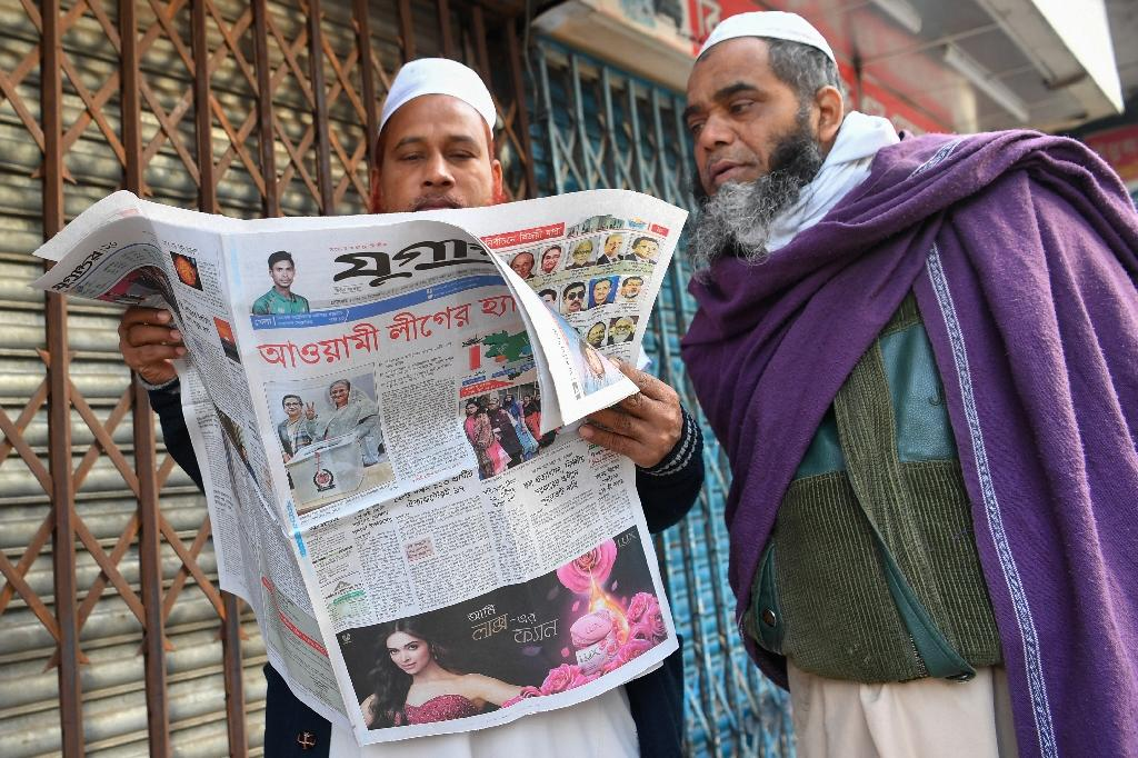 Bangladeshis read about the election result in the newspapers on December 31 (AFP Photo/Indranil MUKHERJEE)