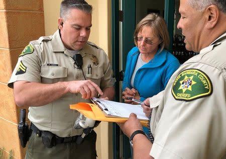 Handout photo of Santa Barbara County Deputies Harris and Rivas talk with a resident, advising of mandatory evacuation notice due to forecasted rain and possible debris flow, near Carpinteria