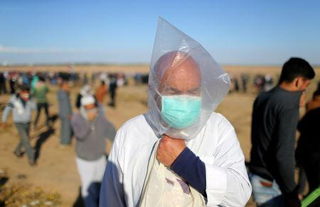 A Palestinian covers his face with a plastic bag to protect himself from tear gas fired by Israeli troops during a protest at the Israel-Gaza border fence, in the southern Gaza Strip May 3, 2019. REUTERS/Ibraheem Abu Mustafa