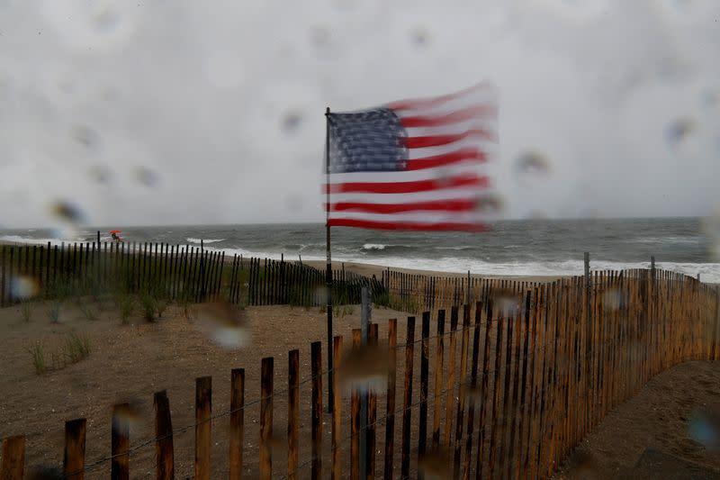 A U.S. flag blows in heavy wind at the beach, as Tropical Storm Fay was expected to sweep across the heavily populated northeastern United States, in the Rockaways section of the Queens borough of New York