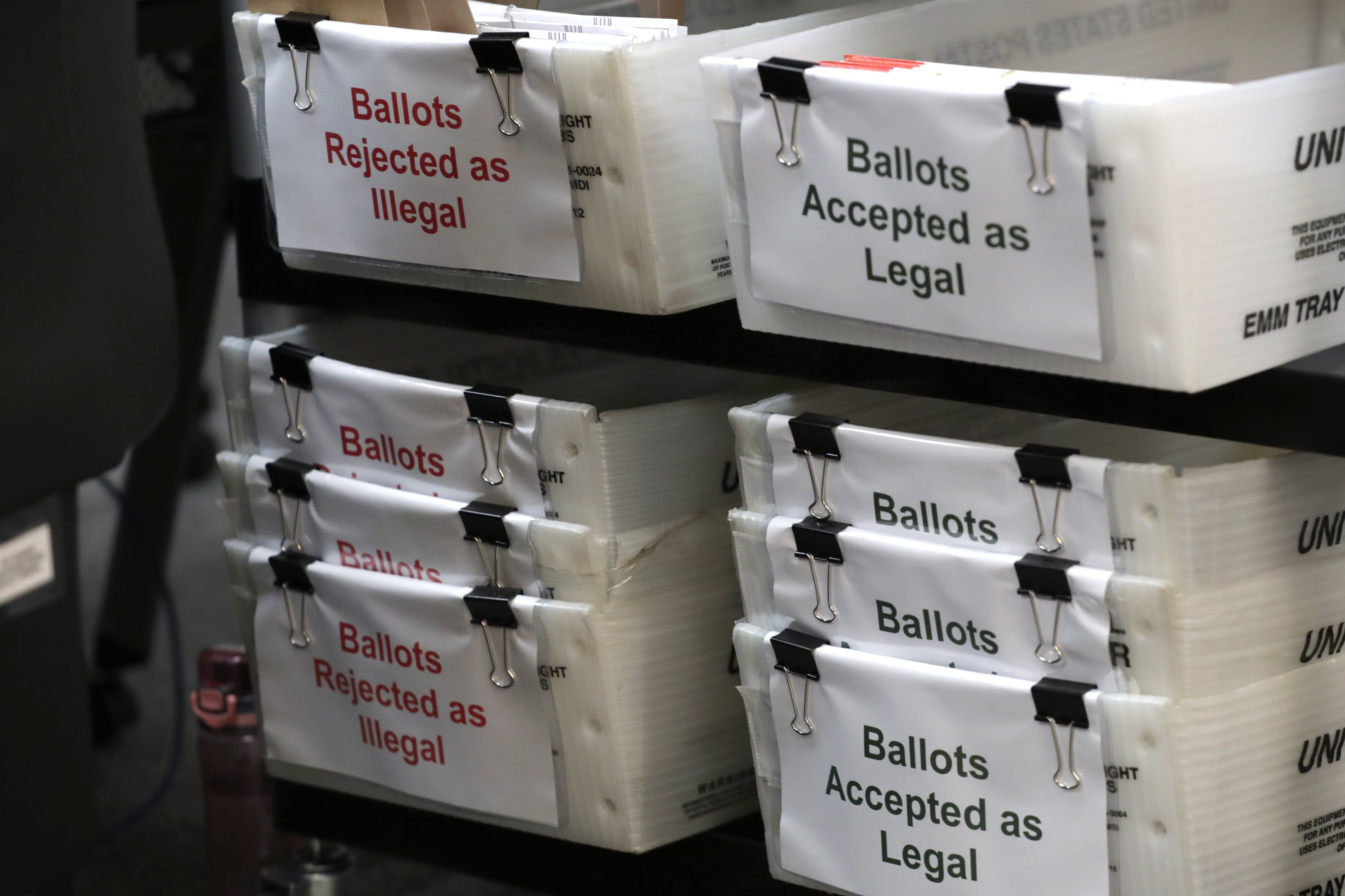 """Boxes for illegal and legal vote-by-mail ballots are shown as the the Miami-Dade County canvassing board meets to verify signatures on vote-by-mail ballots for the August 18 primary election at the Miami-Dade County Elections Department, Thursday, July 30, 2020, in Doral, Fla. President Donald Trump is for the first time publicly floating a """"delay"""" to the Nov. 3 presidential election, as he makes unsubstantiated allegations that increased mail-in voting will result in fraud. (AP Photo/Lynne Sladky)"""