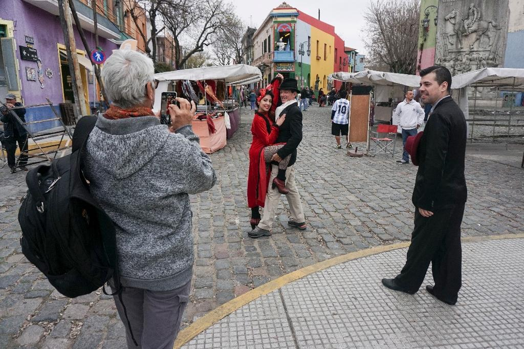 A tourist takes pictures of a couple dancing tango at the traditional street museum Caminito in La Boca neighborhood in Buenos Aires (AFP Photo/Eitan ABRAMOVICH)
