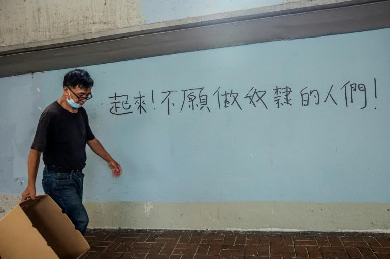 "In the busy shopping district of Causeway Bay, one of the main pro-democracy protest spots last year, newly daubed graffiti declares: ""Arise, ye who refuse to be slaves"" -- the first line of China's national anthem (AFP Photo/ISAAC LAWRENCE)"