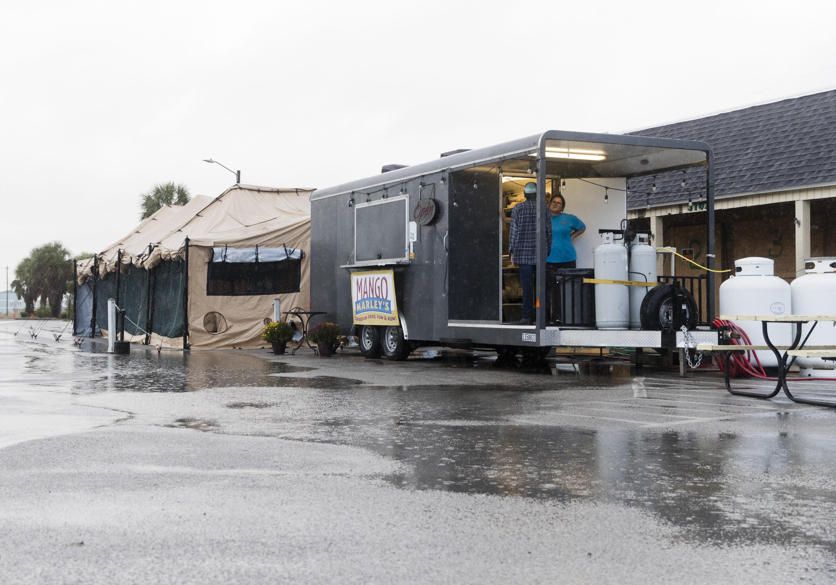 Mango Marley's opens after Tropical Storm Nestor passed Mexico Beach, Fla. on Saturday, Oct. 19, 2019. Nestor was downgraded Saturday after it spawned a tornado that damaged homes and a school in central Florida but spared an area of the Panhandle devastated one year ago by Hurricane Michael. (Joshua Boucher/News Herald via AP)