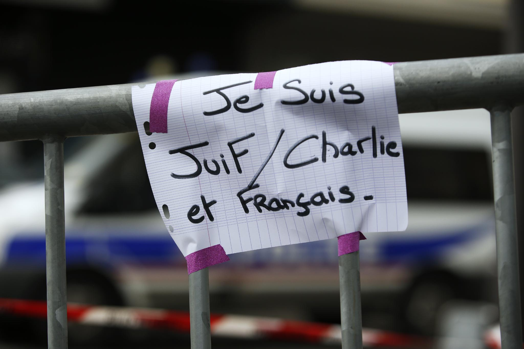 """A sign reading """"I am Jewish, Charlie and French"""" (Je suis Juif, Charle et Francais) is seen near a kosher grocery store in Porte de Vincennes, eastern Paris, on January 10, 2015 a day after four people were killed at the Jewish supermarket"""