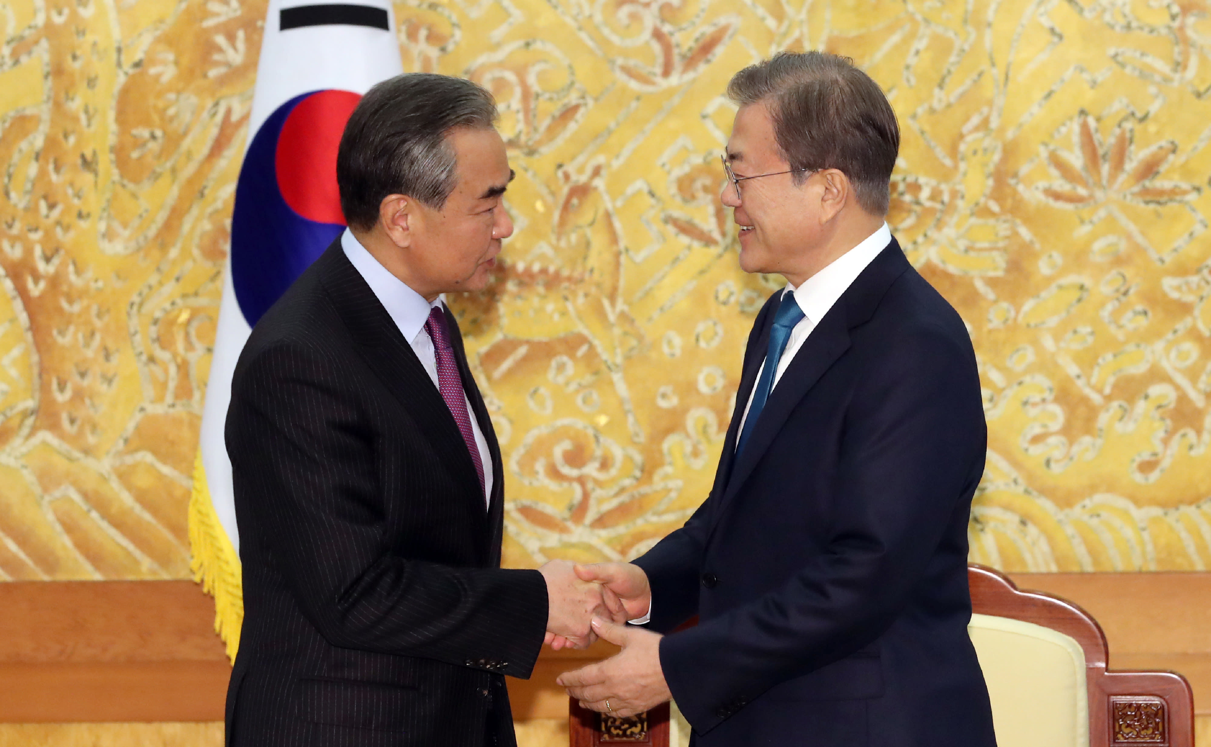 South Korean President Moon Jae-in, right, greets Chinese Foreign Minister Wang Yi during a meeting at the presidential Blue House in Seoul, South Korea, Thursday, Dec. 5, 2019. Wang arrived in South Korea on Wednesday for his first visit in four years amid efforts to patch up relations damaged by Seoul's decision to host a U.S. anti-missile system that Beijing perceives as a security threat. (Lee Jin-wook/Yonhap via AP)
