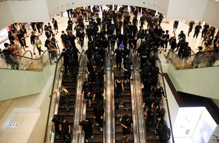 Anti-government protesters ride escalators during a demonstration at New Town Plaza shopping mall in Hong Kong