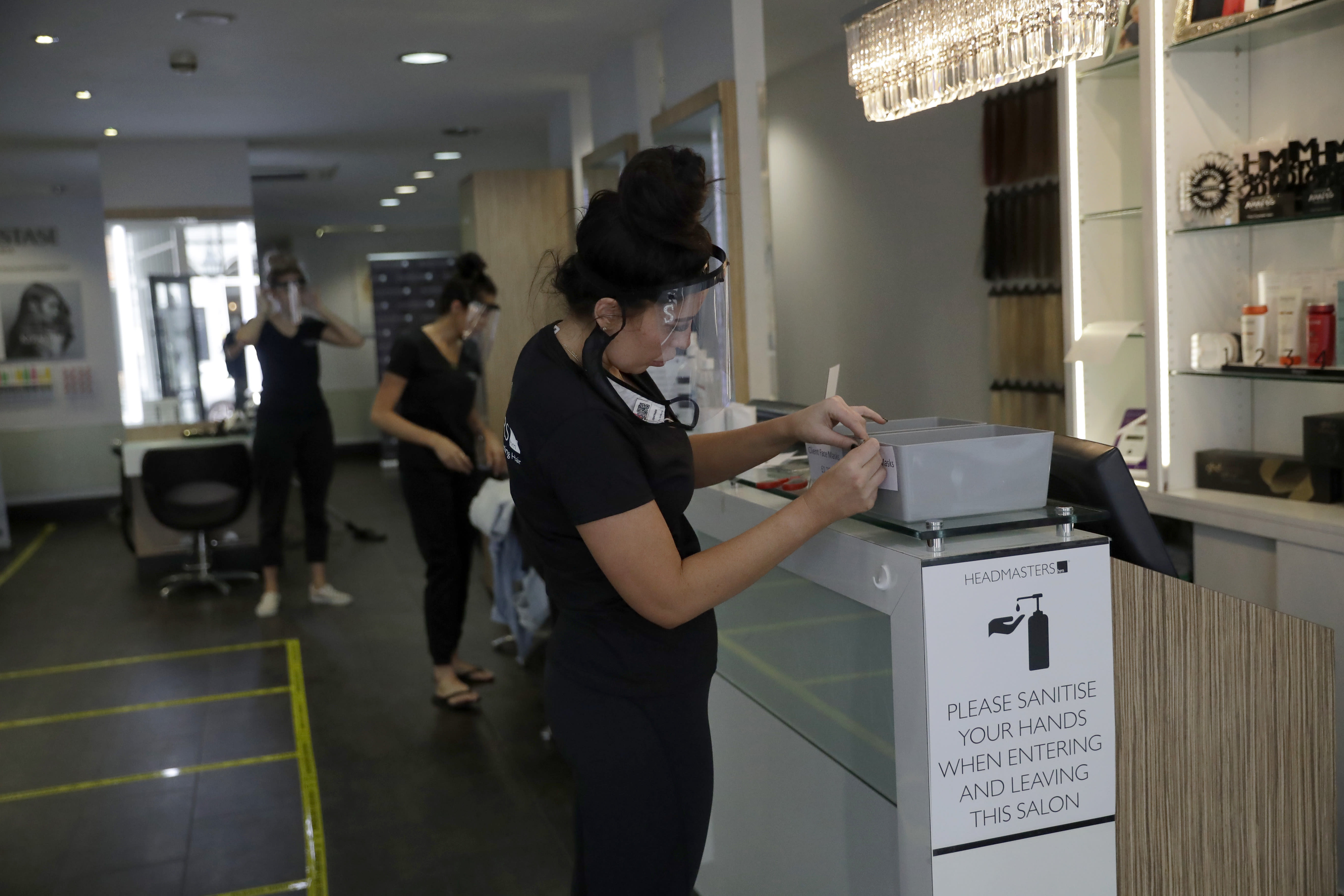 Salon owner Sian Rose Maclaren, right, sticks a label on a box that will house masks clients can buy if they don't already have one, as they prepare to reopen at a franchise branch of the Headmasters group of hairdressing salons, in Surbiton, south west London, Thursday, July 2, 2020. Millions of people in Britain will be able to go to the pub, visit a movie theater, get a haircut or attend a religious service starting July 4, in a major loosening of coronavirus lockdown restrictions. (AP Photo/Matt Dunham)