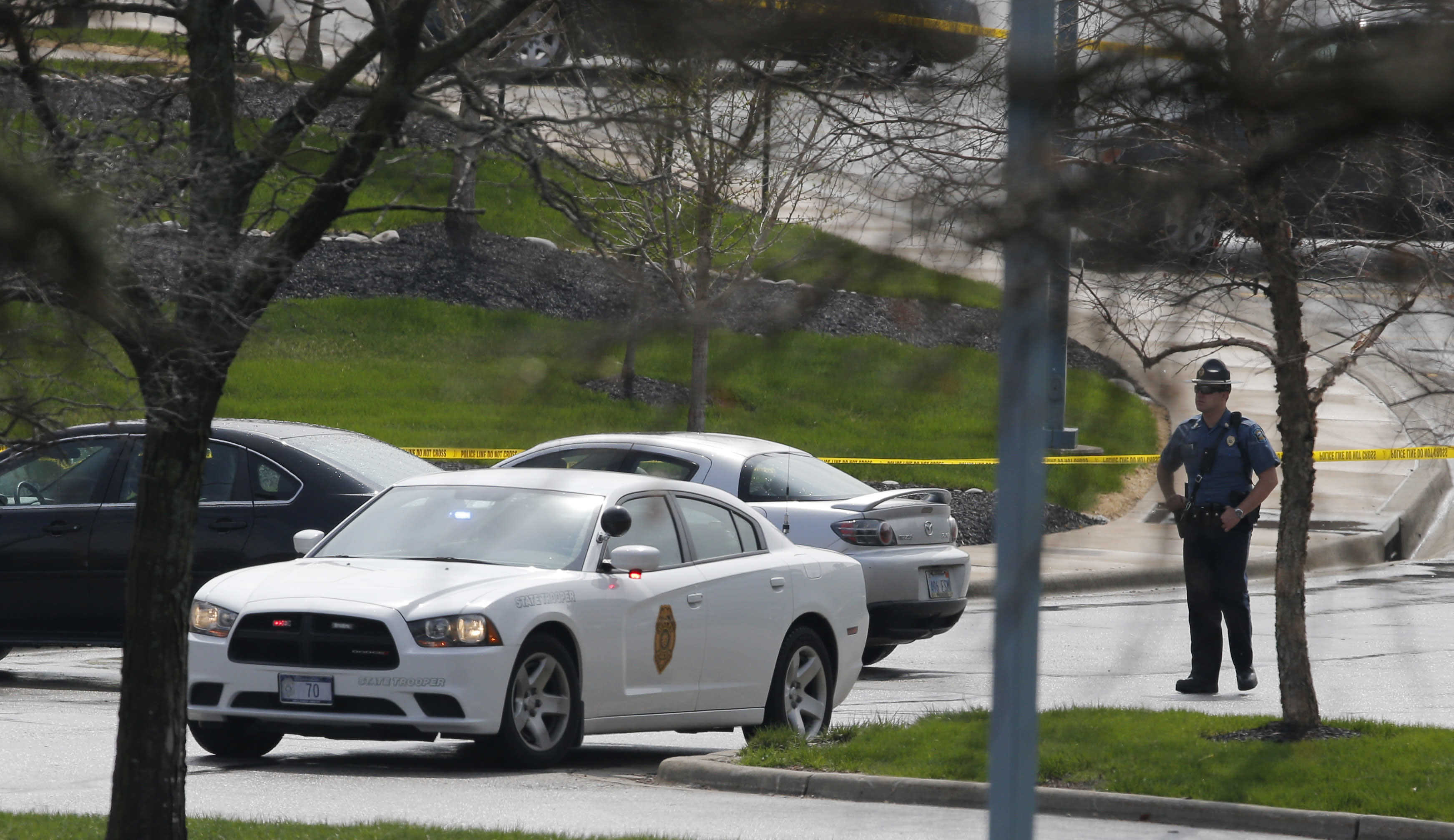 A Kansas State Trooper stands near the location of a shooting at the Jewish Community Center in Overland Park, Kan., Sunday, April 13, 2014. (AP Photo/Orlin Wagner)