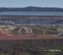 Water flows over the emergency spillway at the tallest US dam